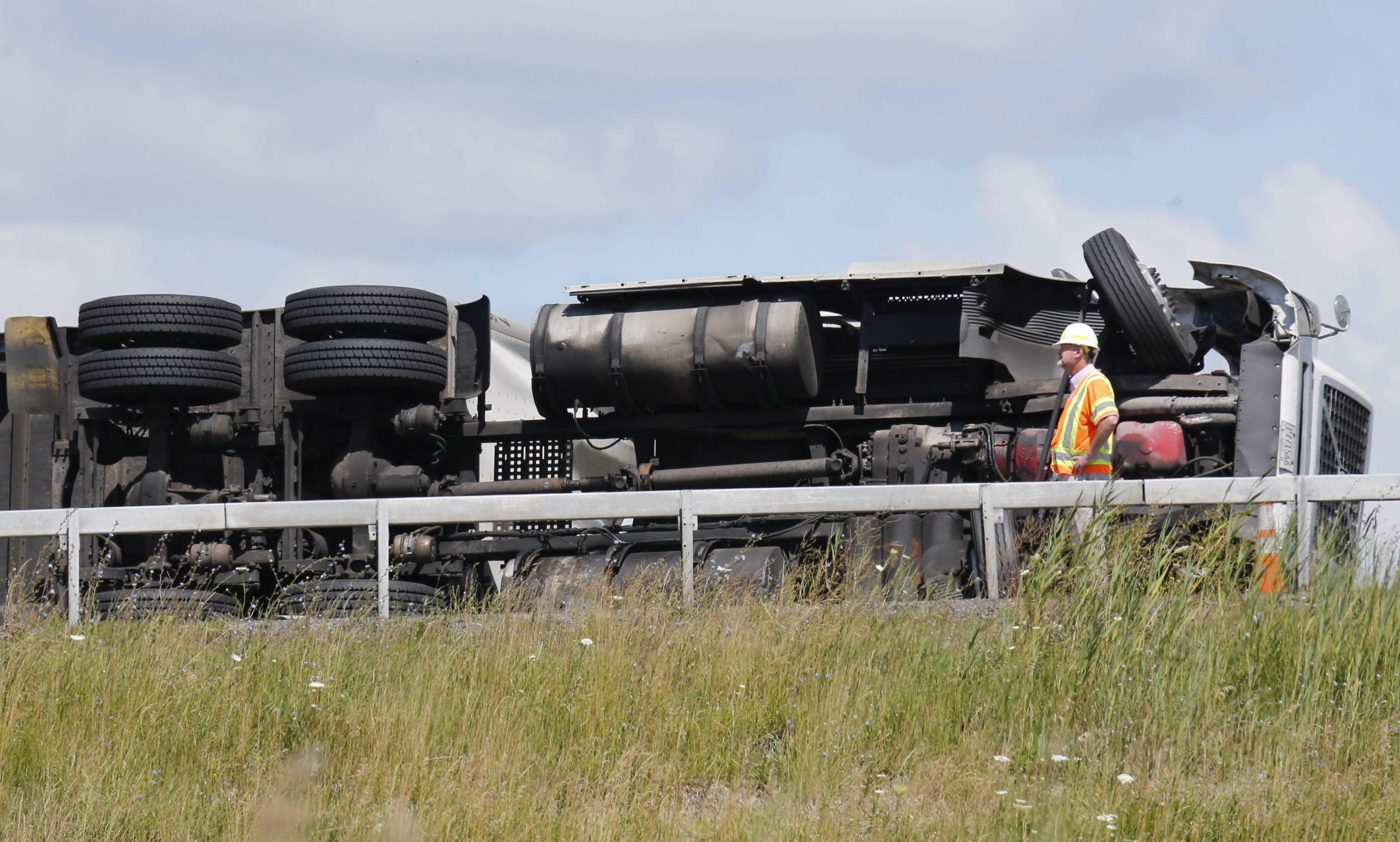 A tractor-trailer rests on its side after a rollover crash on the on-ramp to the I-190 northbound from the eastbound Thruway on July 17.