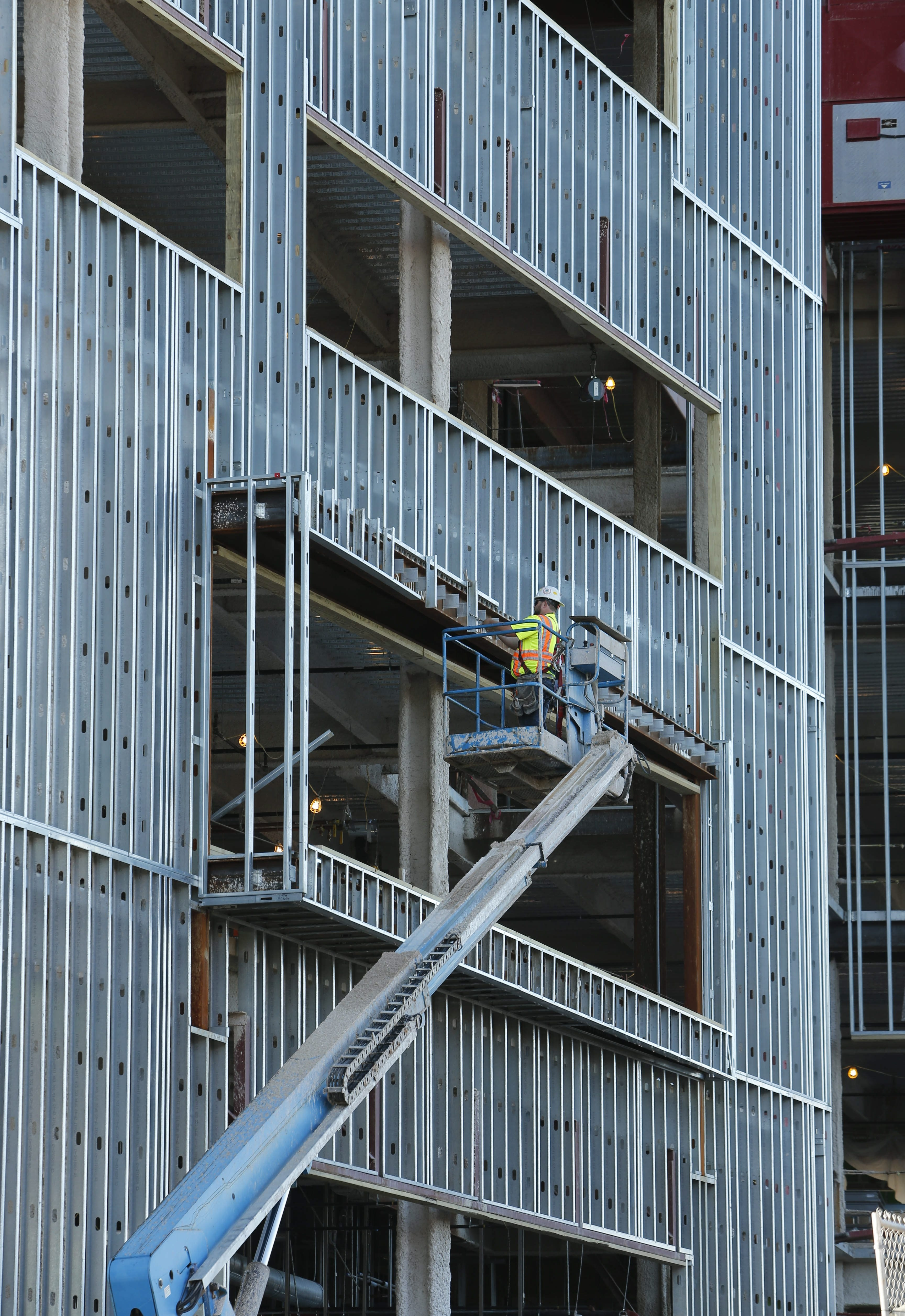 A worker uses a lift while installing the facade of the new Conventus Building.