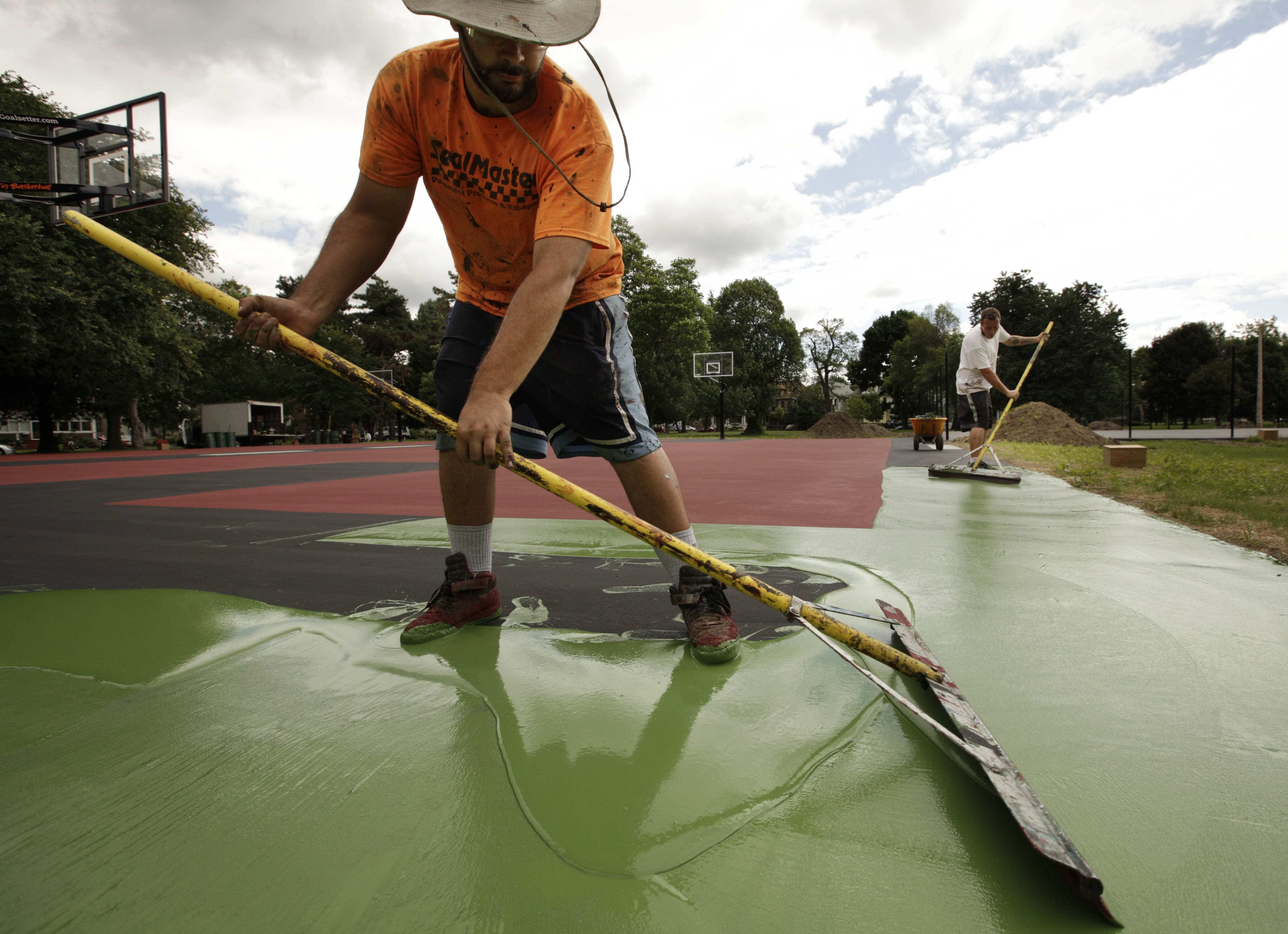 Michael L. Cabrera, left, and Edwin Collins of Sportscourt, spread a coat of specially formulated paint on the basketball court while surfacing the courts in Cazenovia Park today.