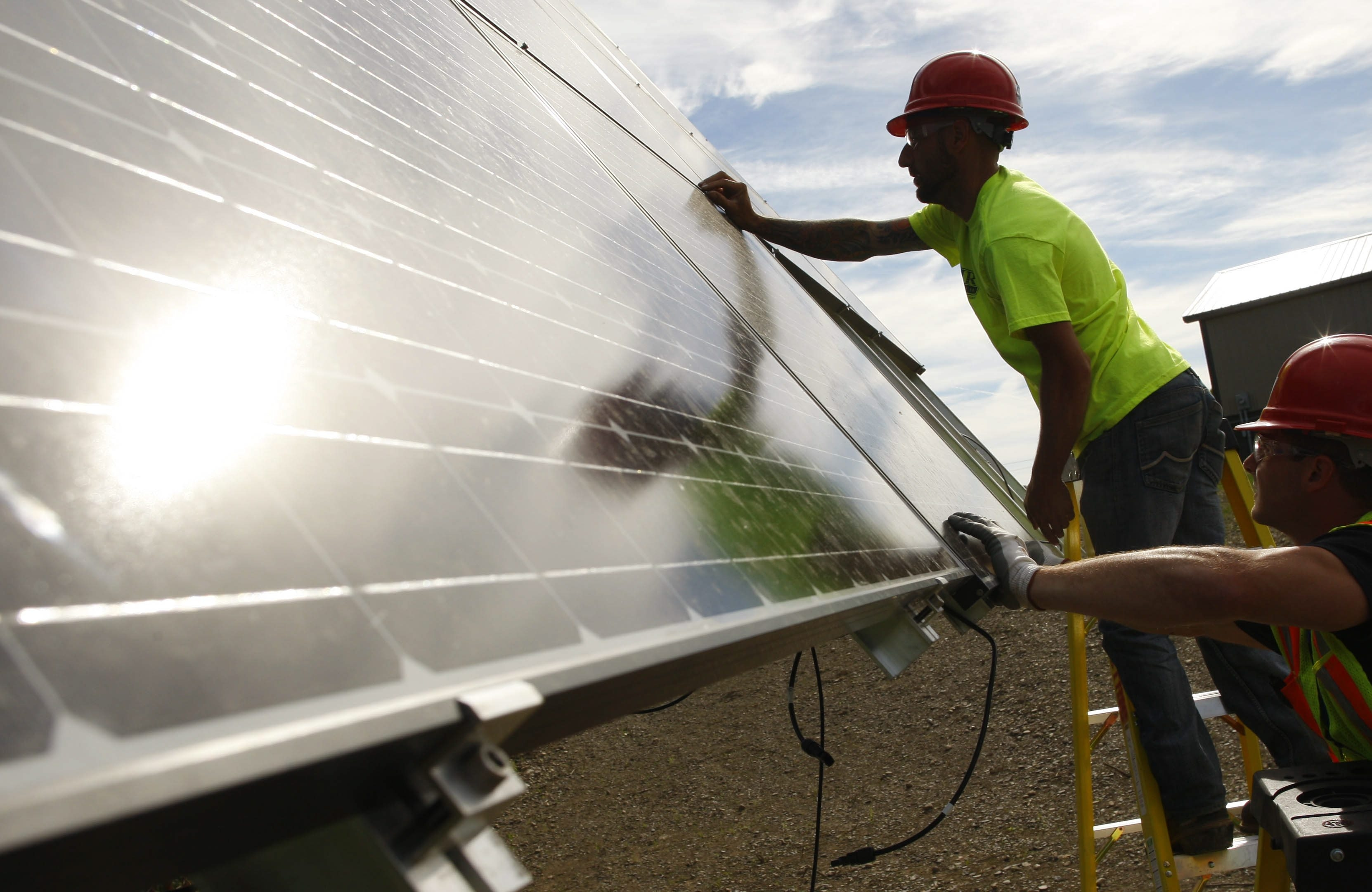 """Electrician Joe Kilijanski, left, and Edward Sarcione of CIR Electrical Construction Corp. install an array of solar panels made by Silevo on a """"tracker"""" system that automatically follows the sun to optimize the system's performance at a residence in Marilla on June 20."""