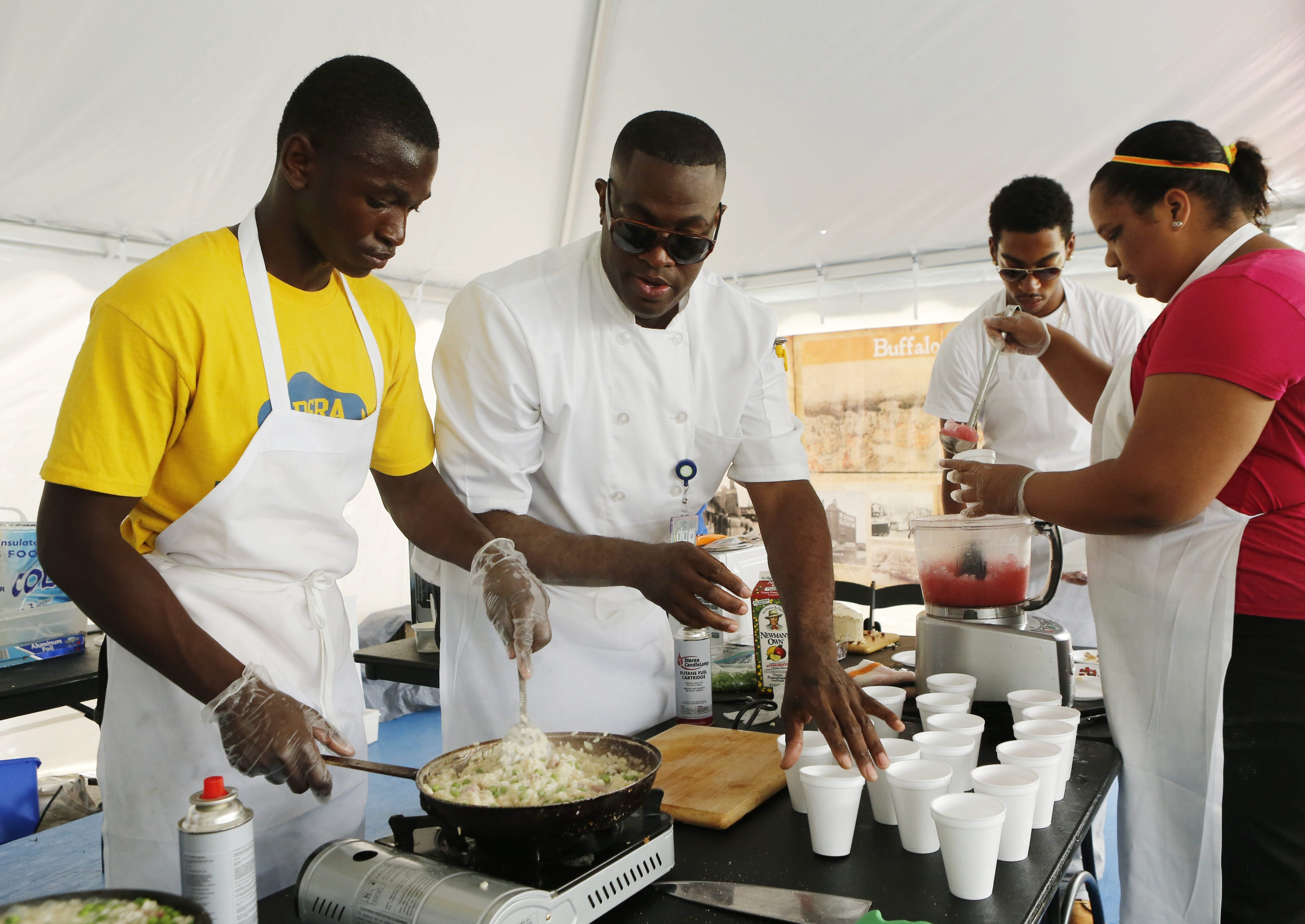 """Local chef Bobby Anderson, a former """"Hell's Kitchen"""" contestant, helps F Bites participants prepare a meal at Canalside on Tuesday."""