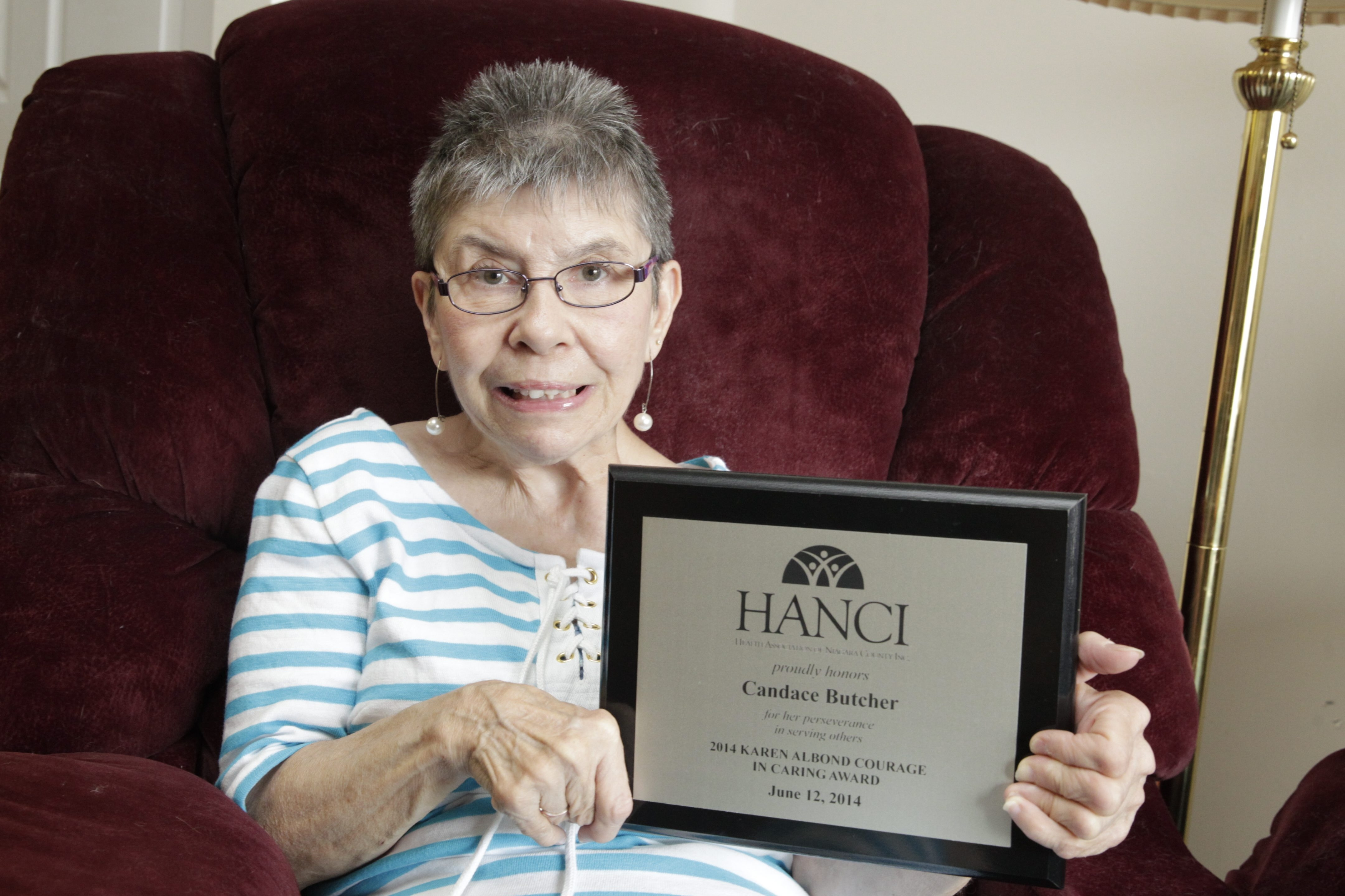 Candace Butcher, who has been a volunteer helping others with cerebral palsy despite her own challenges, displays the award she recently won for her service.