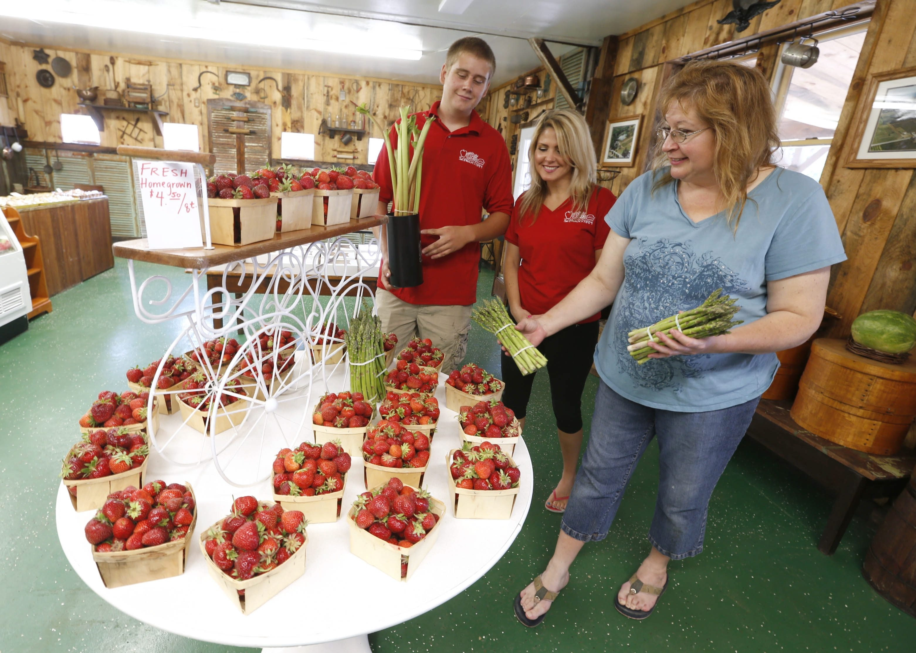 Sanger Farms owner  Sandra Tuck, right, with some fresh picked strawberries and asparagus. She is with her children Shari Posa, center, and Claitan Tuck at their Youngstown store.
