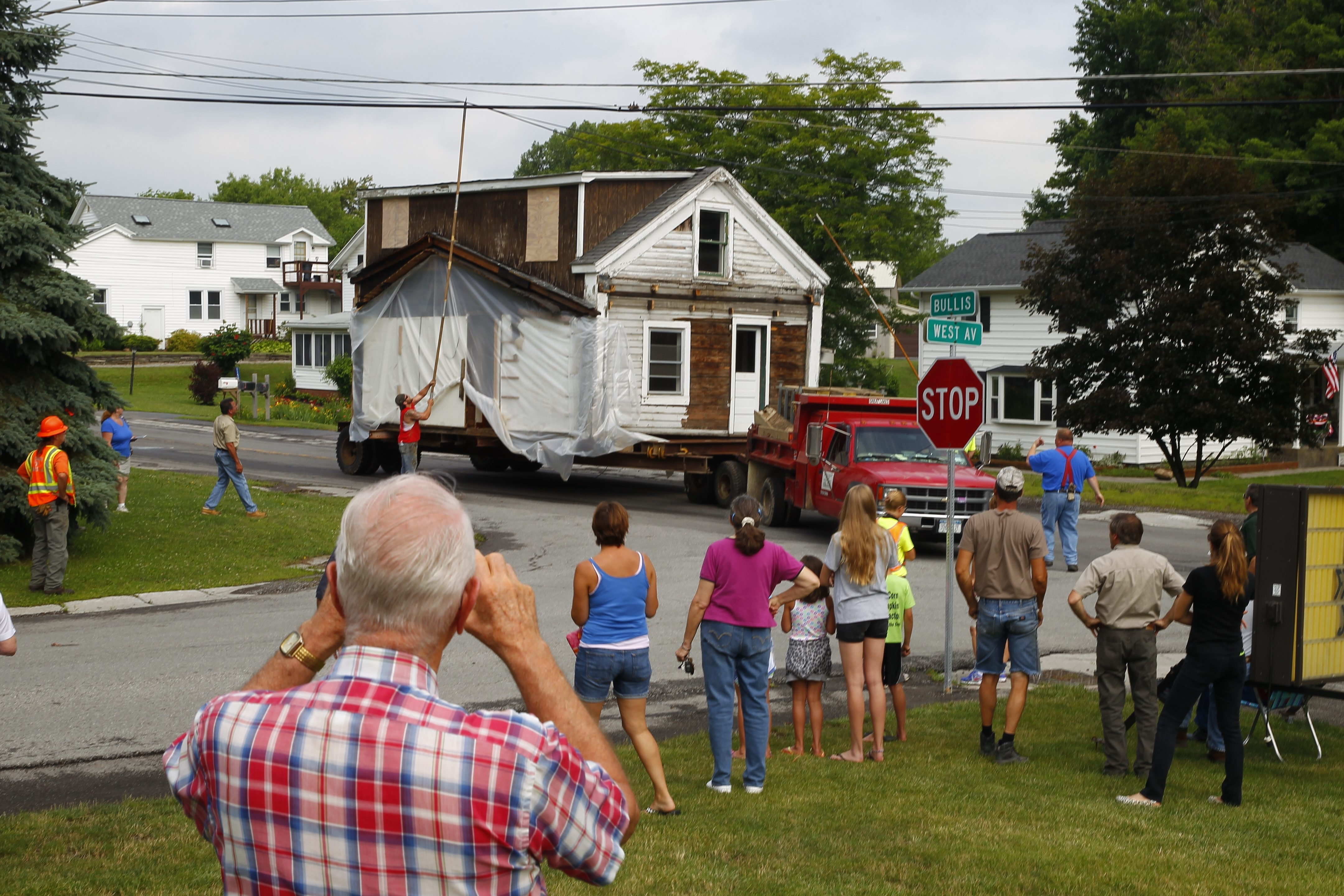 Utility lines are lifted as a log cabin is moved from Bullis Road to West Avenue in Marilla. Photo gallery at BuffaloNews.com.