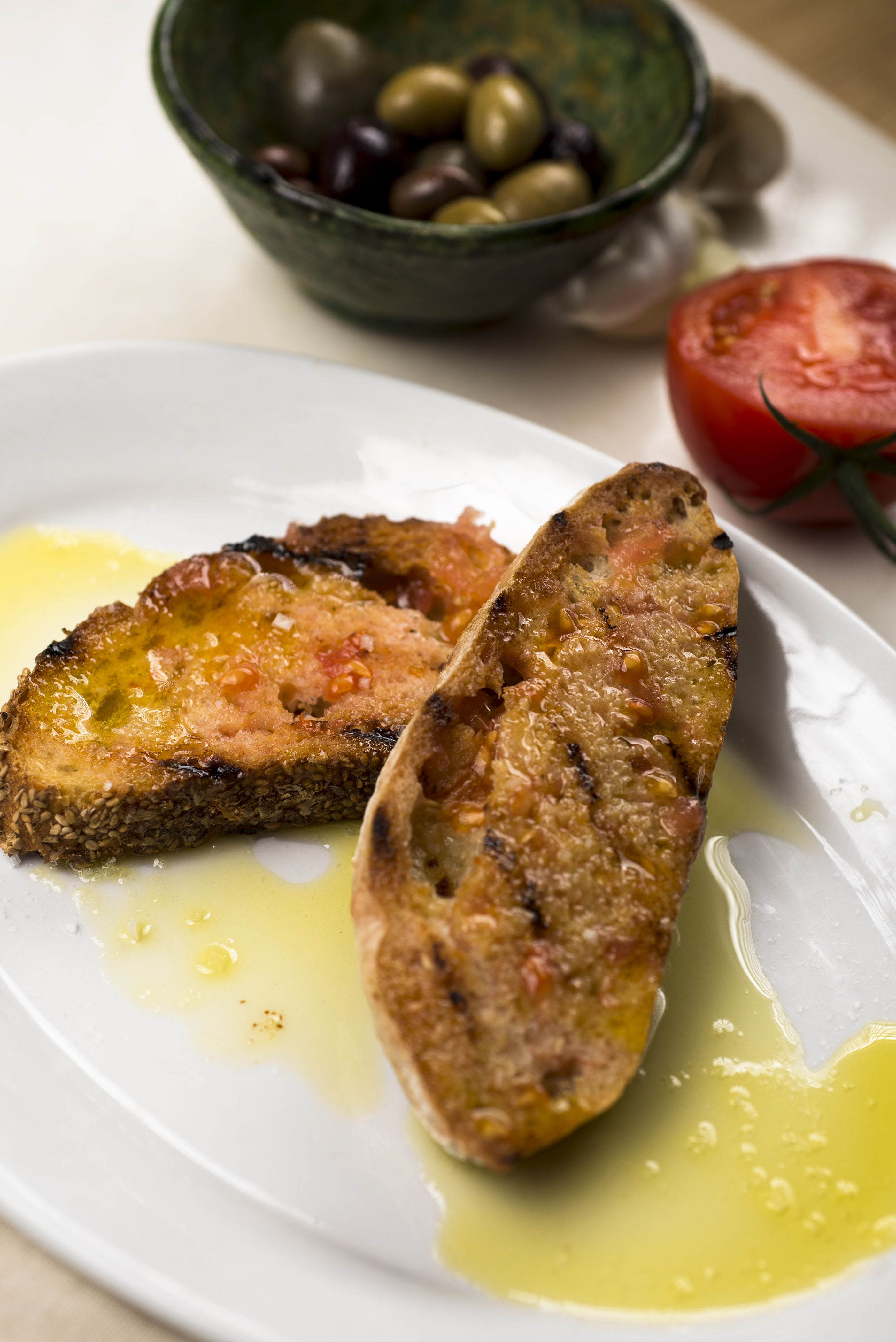 Grilled bread is rubbed with garlic and tomato, and drizzled with olive oil.