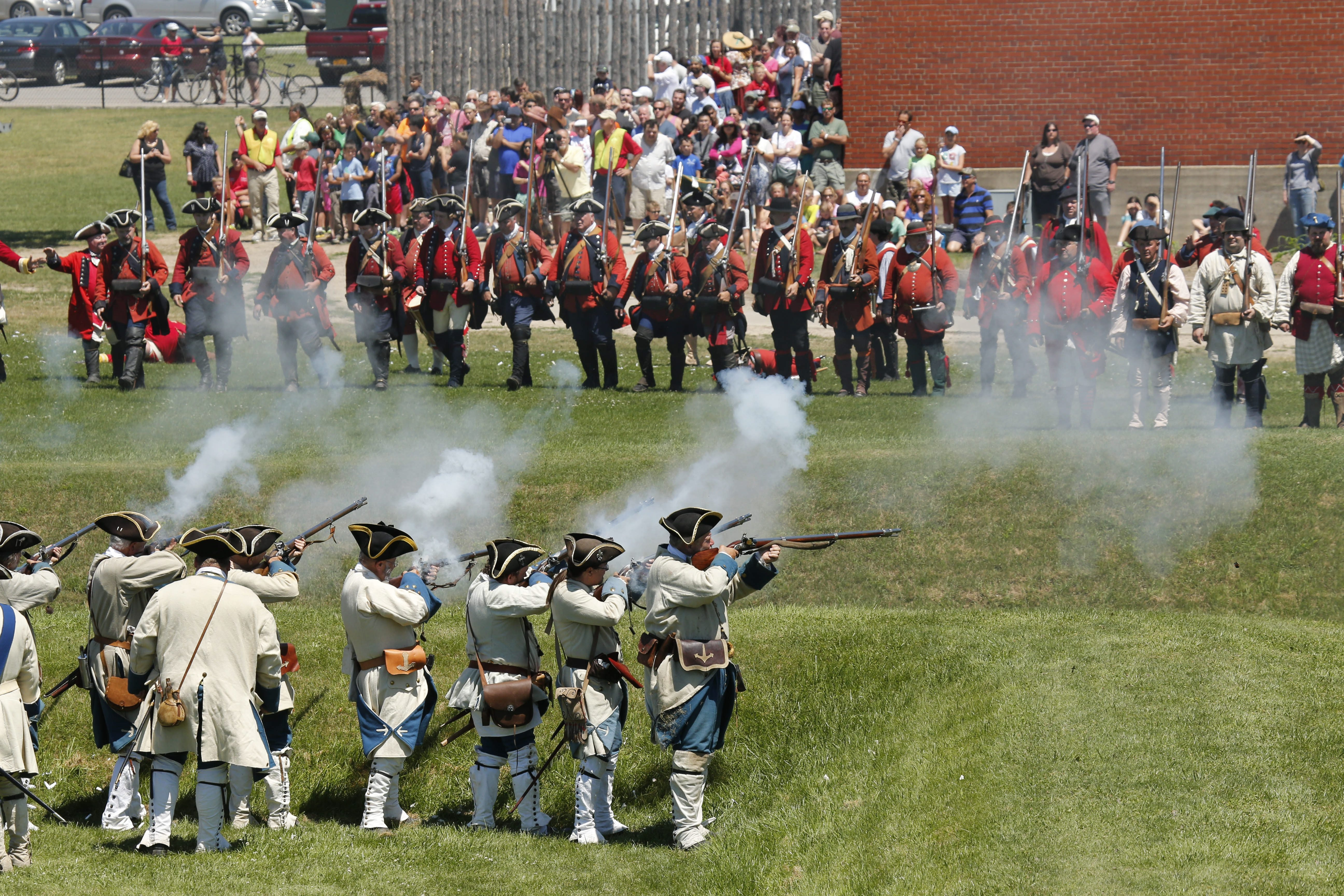 Re-enactors portraying French and British troops exchange fire during the 35th annual French and Indian War Encampment at Old Fort Niagara on Saturday.