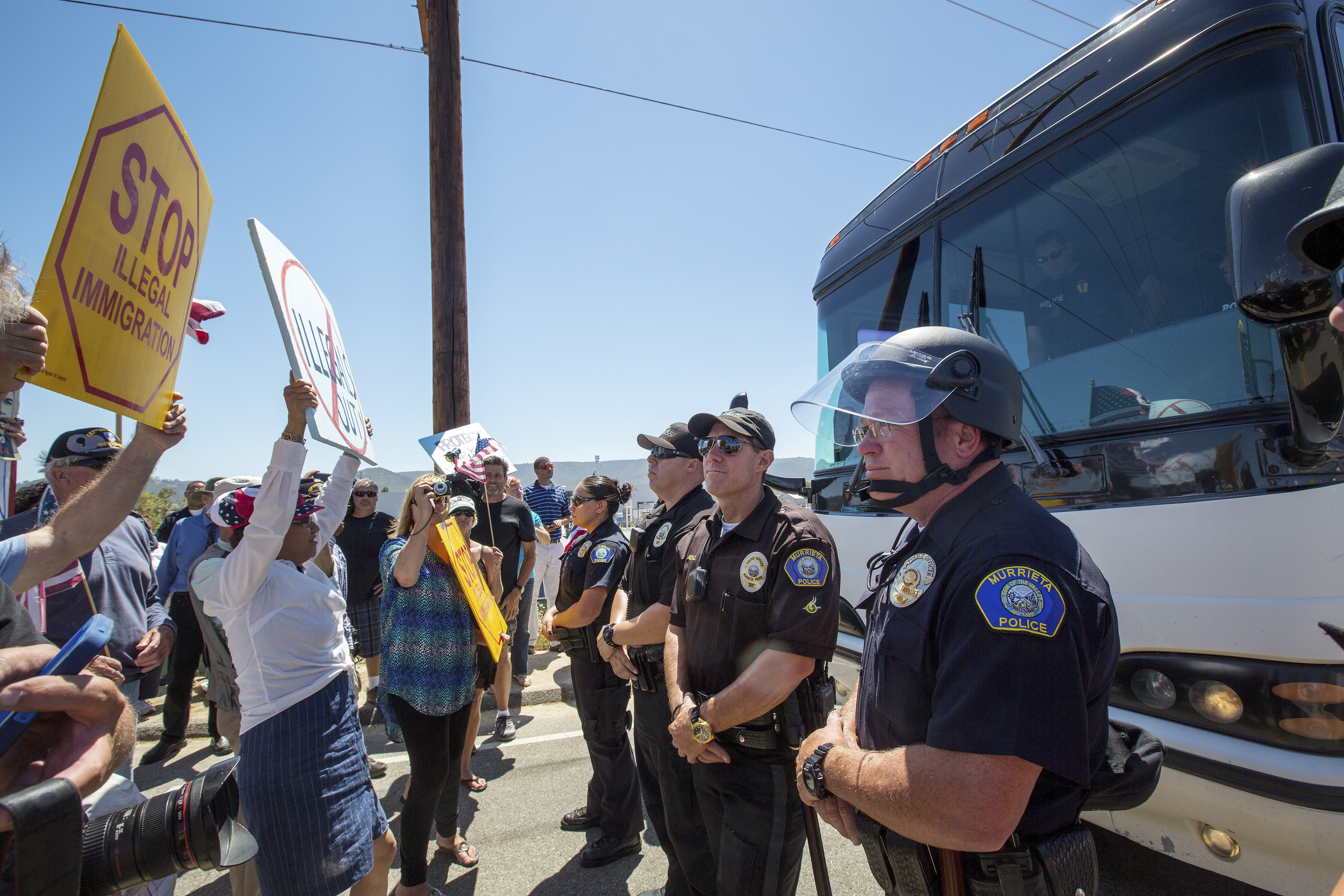 Anti-immigration protesters in Murrieta, calif., block a bus of migrants transferred from overcrowded facilities in Texas. (New York Times photo)