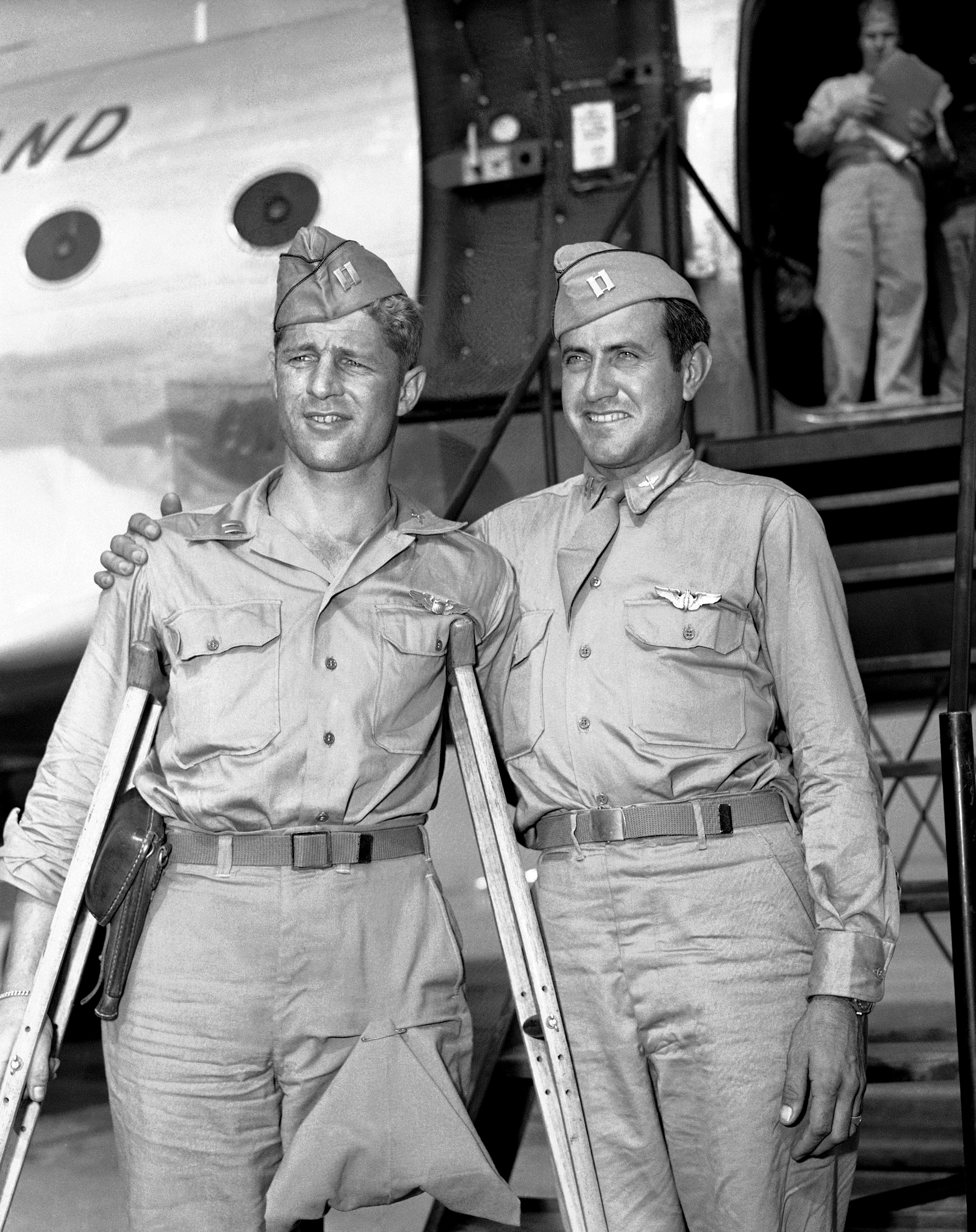 In a Oct. 3, 1945 file photo, Capt. Louis Zamperini (right), Torrence, Calif., former track star, who was adrift 47 days in Pacific after bombing mission against the Japanese and presumed dead, stands with his Pal, Capt. Fred Garrett, Riverside, Calif., upon  their arrival at Hamilton Field, Calif. Both were prisoners of war. Zamperini, a U.S. Olympic distance runner and World War II veteran who survived 47 days on a raft in the Pacific after his bomber crashed, then endured two years in Japanese prison camps, died Wednesday, July 2, 2014, according to Universal Pictures studio spokesman Michael Moses. He was 97. (AP Photo/PCS, File)