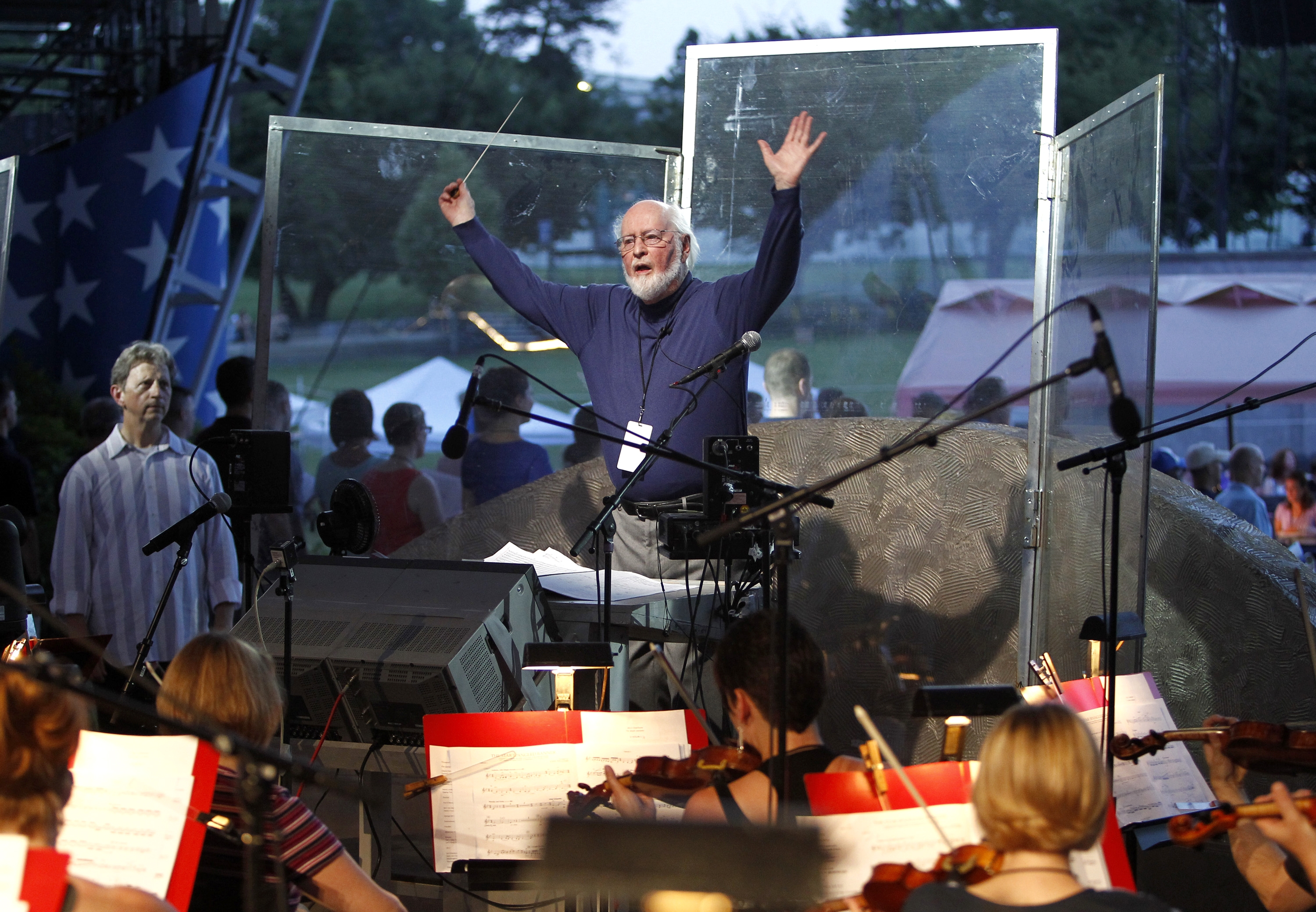 Conductor John Williams rehearses Wednesday with the National Symphony Orchestra and others for tonight's debut of a new arrangement of the national anthem.