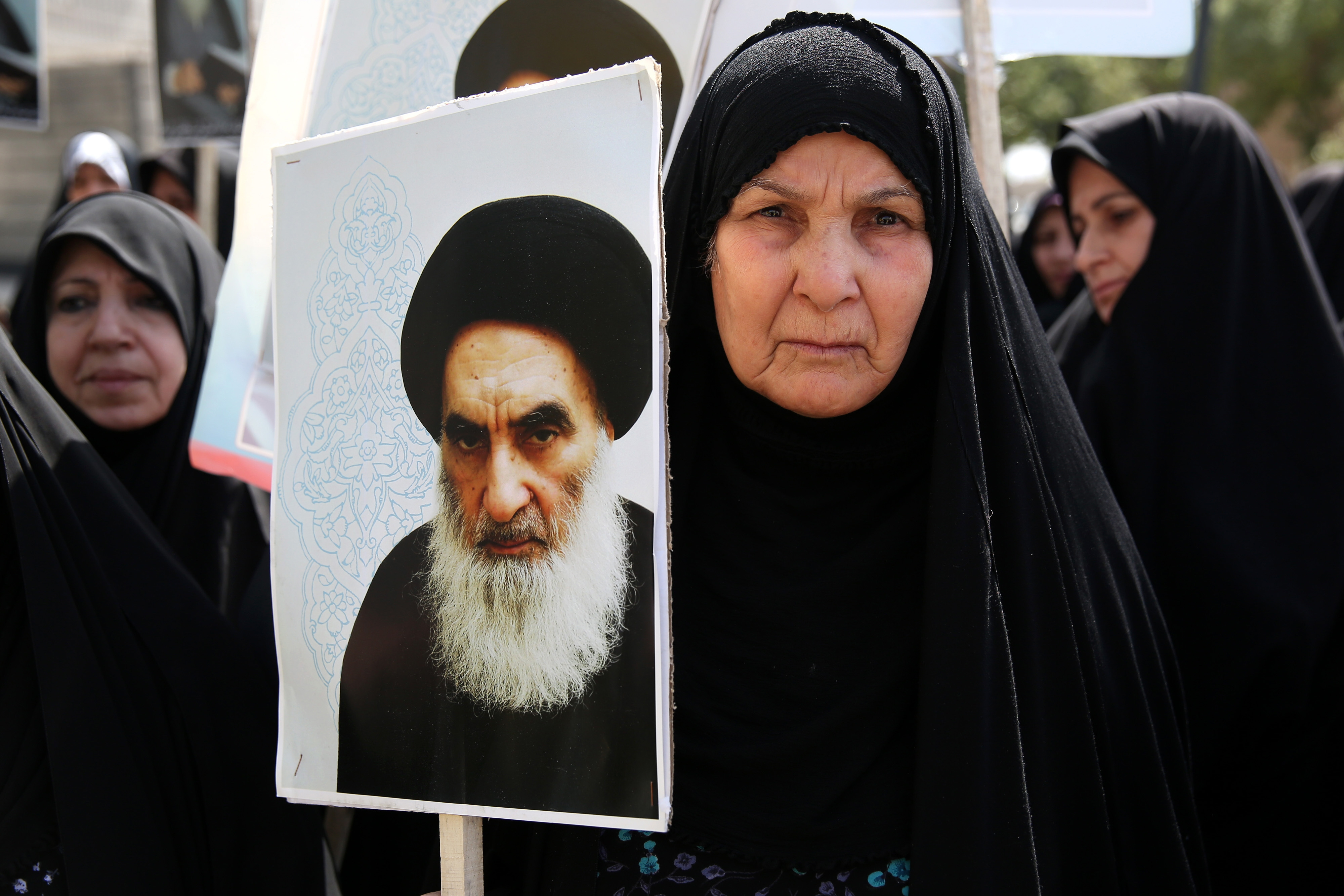An Iraqi woman living in Iran holds a poster of the Grand Ayatollah Ali al-Sistani, Iraq's top Shiite cleric, in a demonstration against Sunni militants of the al-Qaida-inspired Islamic State of Iraq. Shiite leaders have pushed for the removal of Iraqi Prime Minister Nouri al-Maliki as parliament works on a new government.