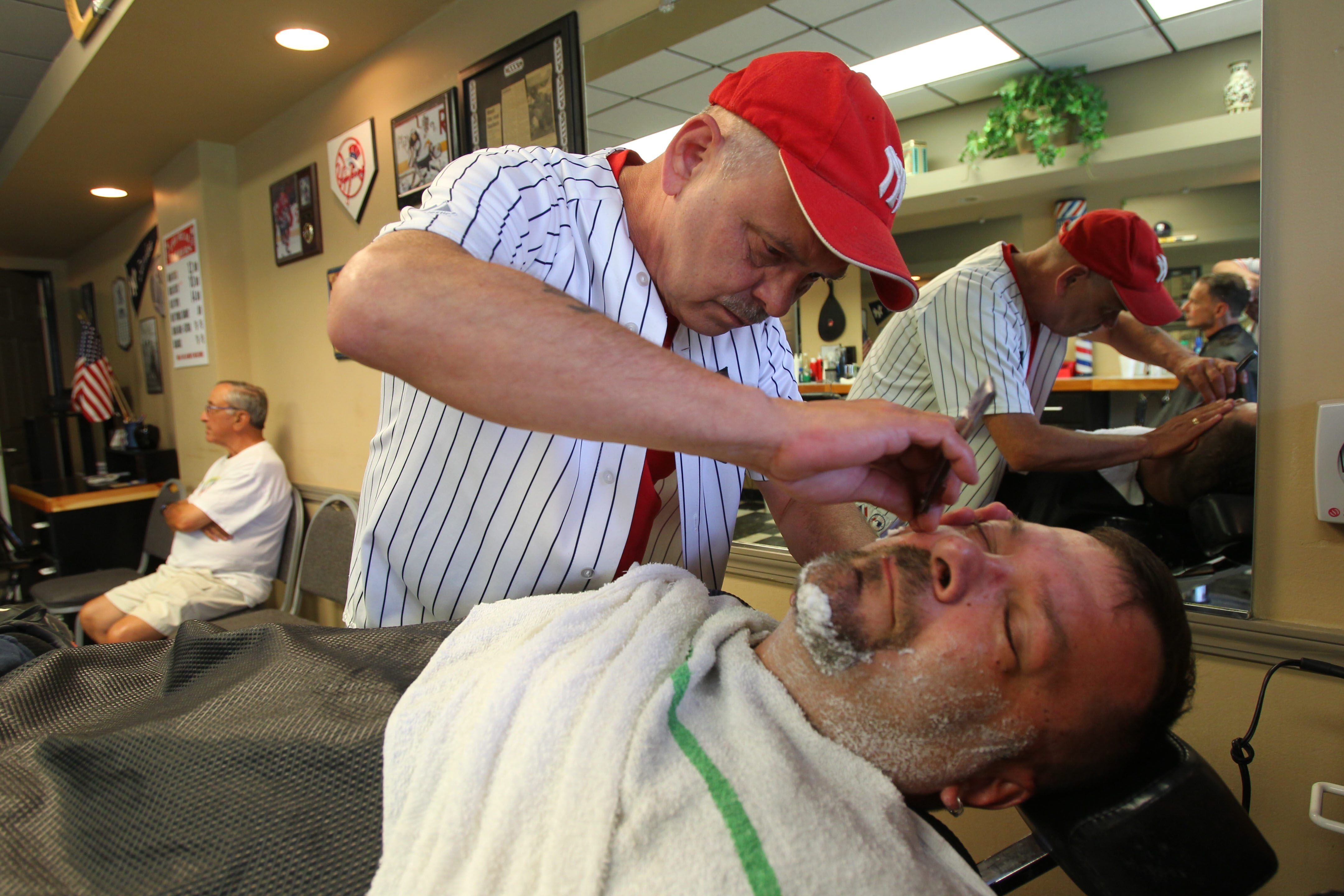 Vetaran barber Rich Rosso focuses closely as he gives a shave to customer Dave Zaleski at the Real Barbers in Kenmore.