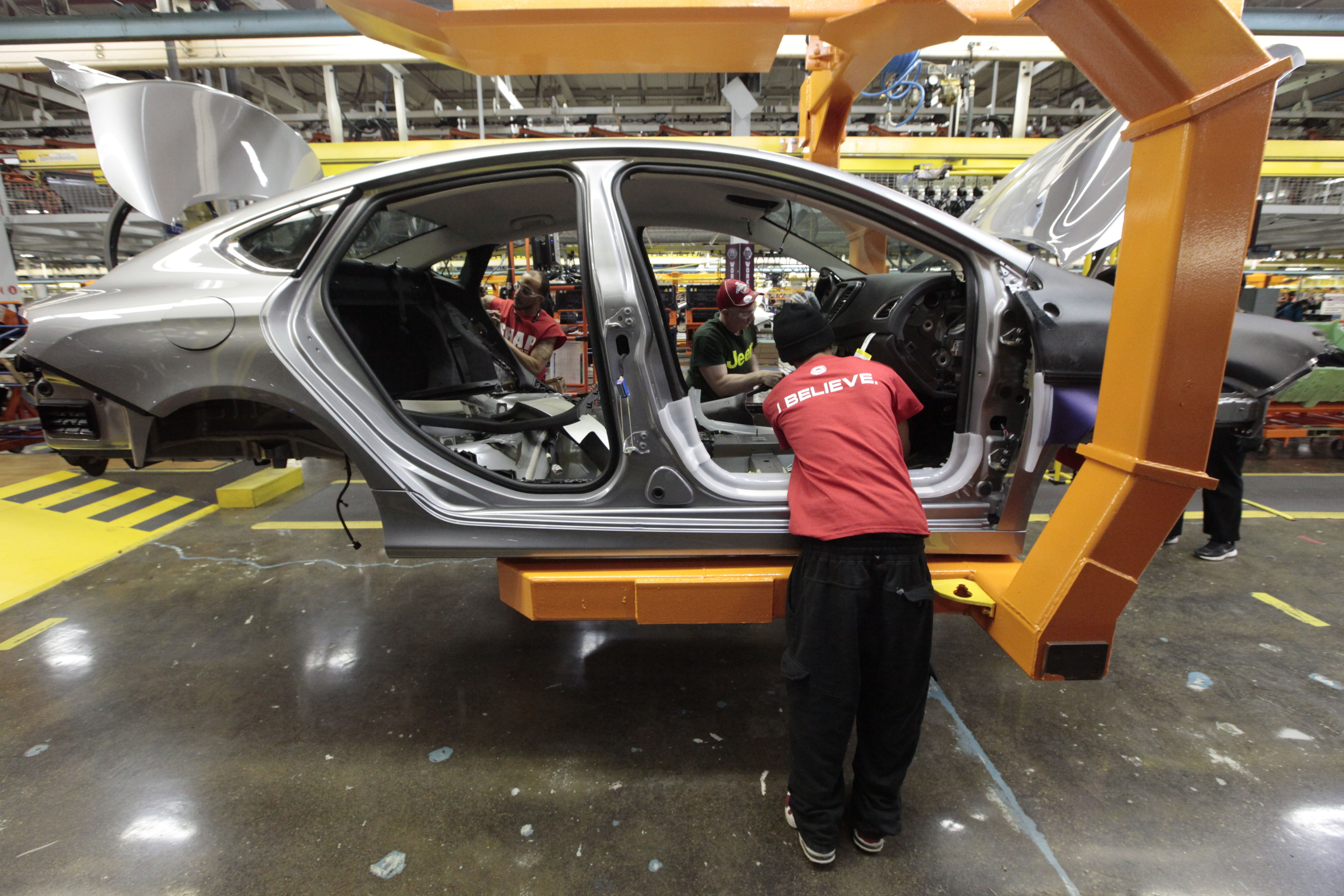 Assembly line workers build a 2015 Chrysler 200 automobile in Sterling Heights, Mich. Chrysler's U.S. auto sales jumped 9 percent in June, the company reported Tuesday.