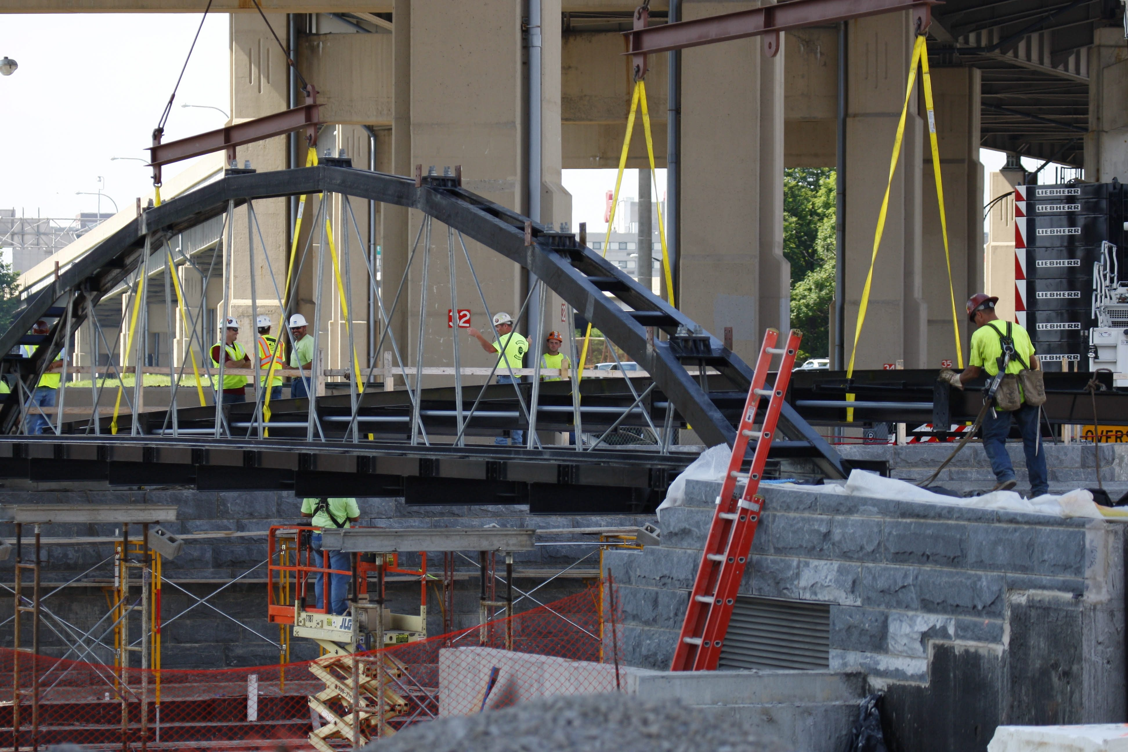 Workers install the first of three bridges at the Canalside site. (Derek Gee/Buffalo News)