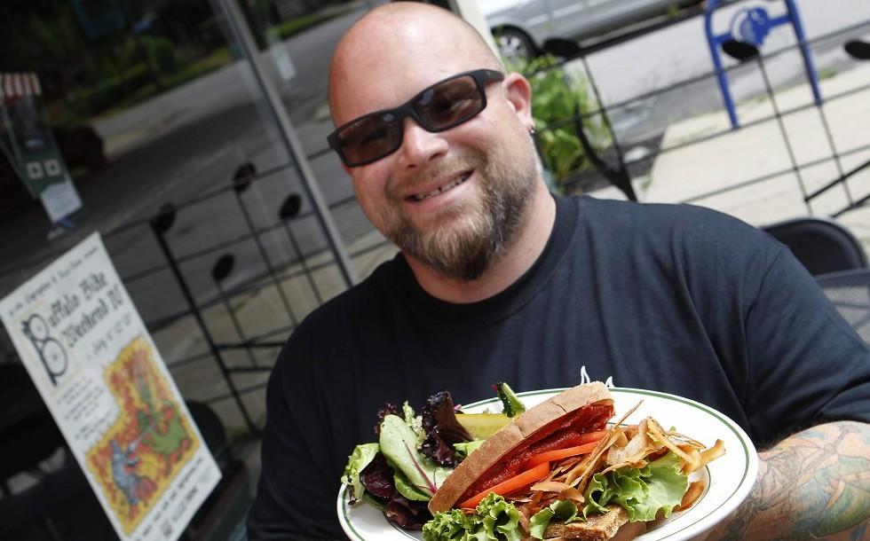 "Essex Street Pub owner James ""Macky"" Moberly presents the vegan club sandwich. (Sharon Cantillon/Buffalo News)"