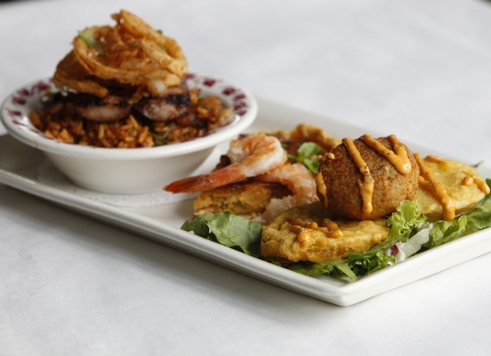 From left, jambalaya with grilled Polish sausage and onion rings; lobster cheesecake with shrimp; and crab cake over fried green tomatoes. (Sharon Cantillon/Buffalo News)