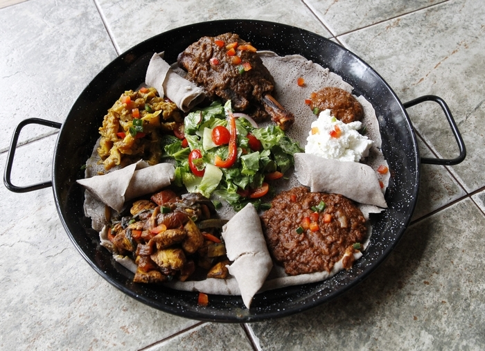 Clockwise from top: Lamb shank, Ethiopian-style cottage cheese, red lentils, spicy chicken breast and potatoes with onion. (Sharon Cantillon/Buffalo News)