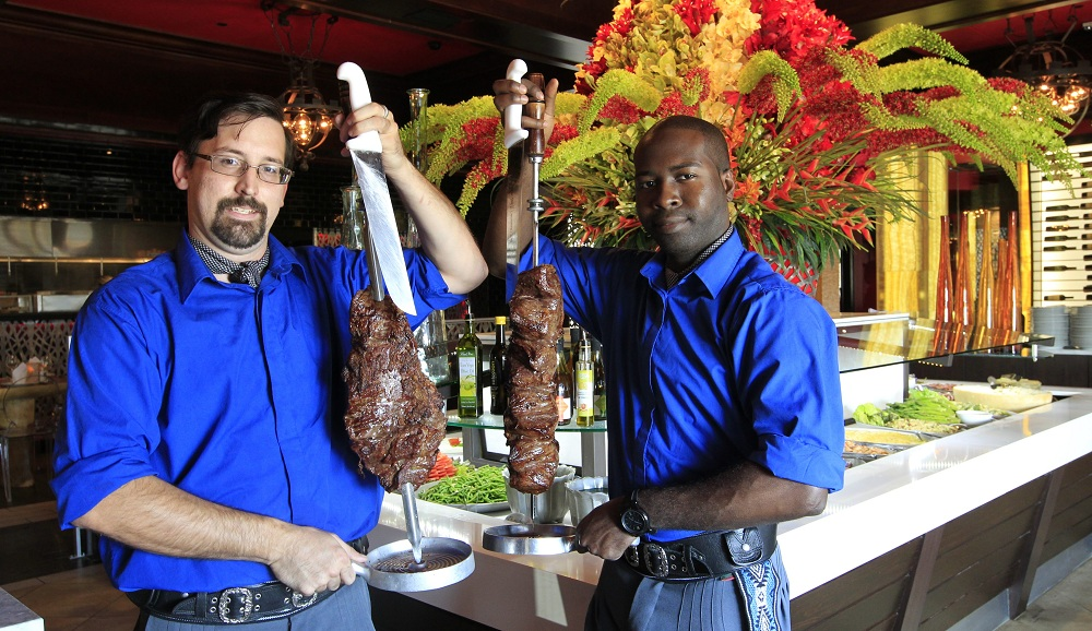 Jimmy Louck (left) holds the flank steak while Blondy Daquin holds the Picanha near the salad bar at Texas de Brazil.(Harry Scull Jr. /Buffalo News)
