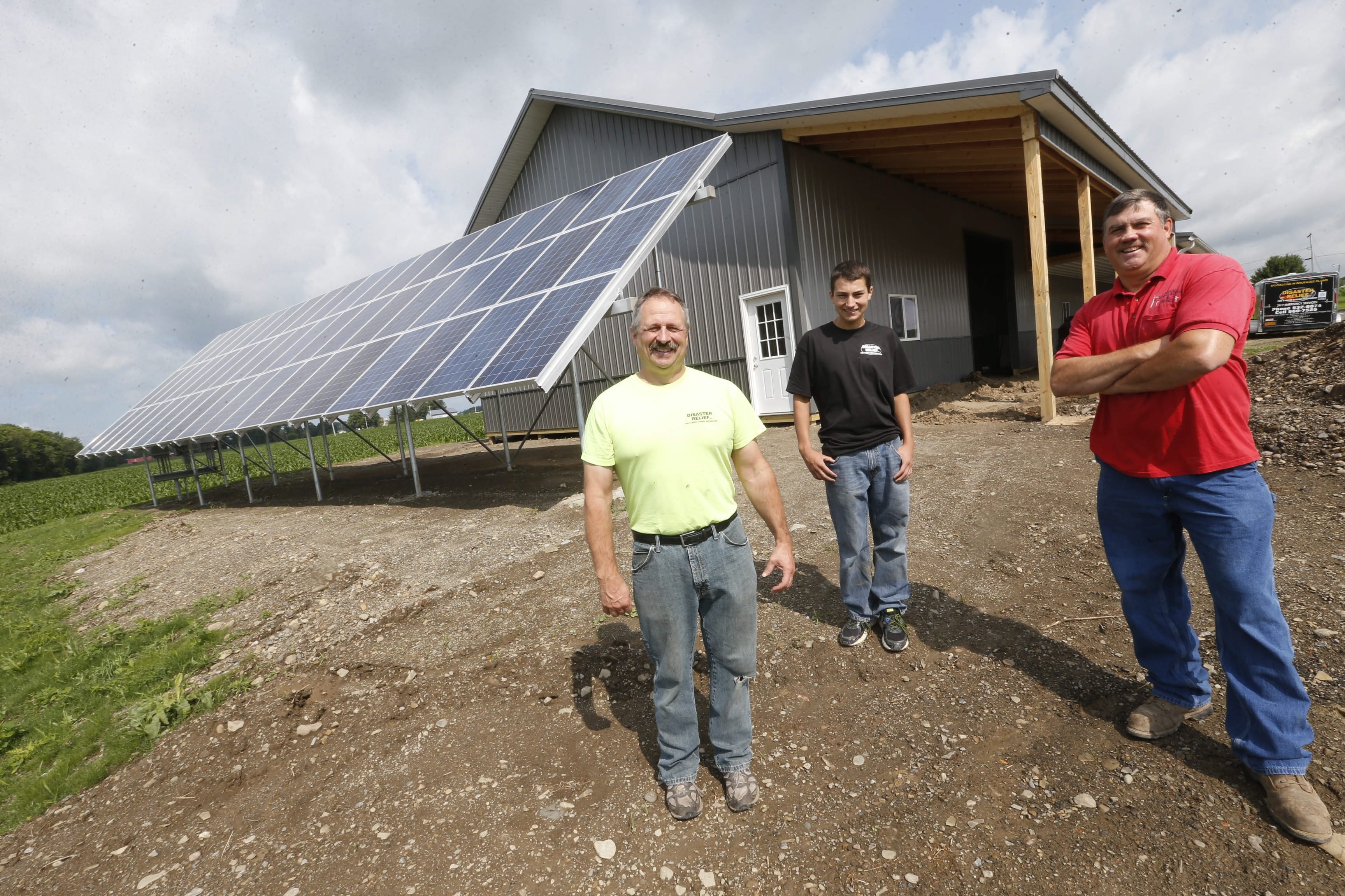 Bob Timmel with his son Dylan, 17, center, and Rodney Weaver, with Rural Generation and Wind Inc., near the panels that power Timmel's electric needs.