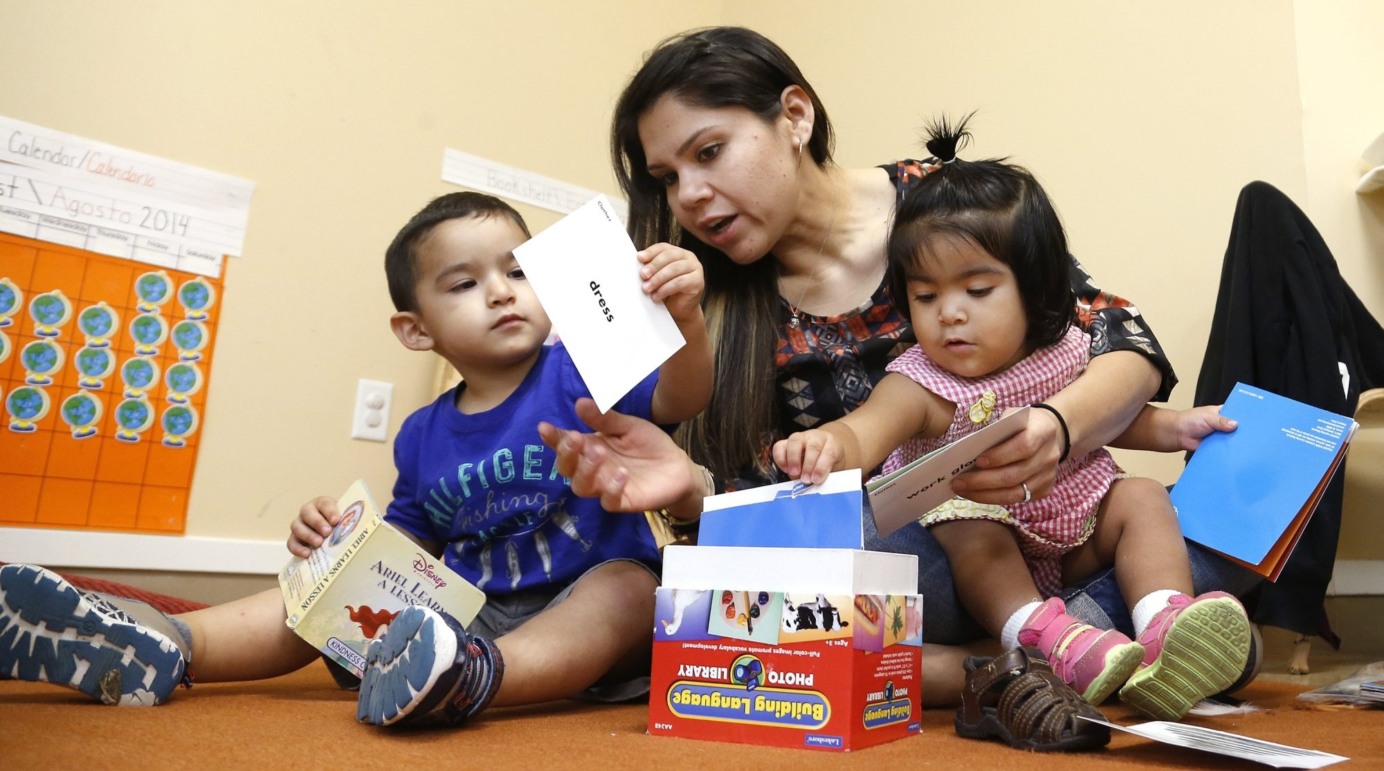Elizabeth Mancilla, center, one of the teachers at the ChildCareGroup in Dallas, helps Martin Correa, left, 2½, and Andrea Ramirez, 19 months, with a learning exercise on Friday. The ChildCareGroup specializes in educating very young children.