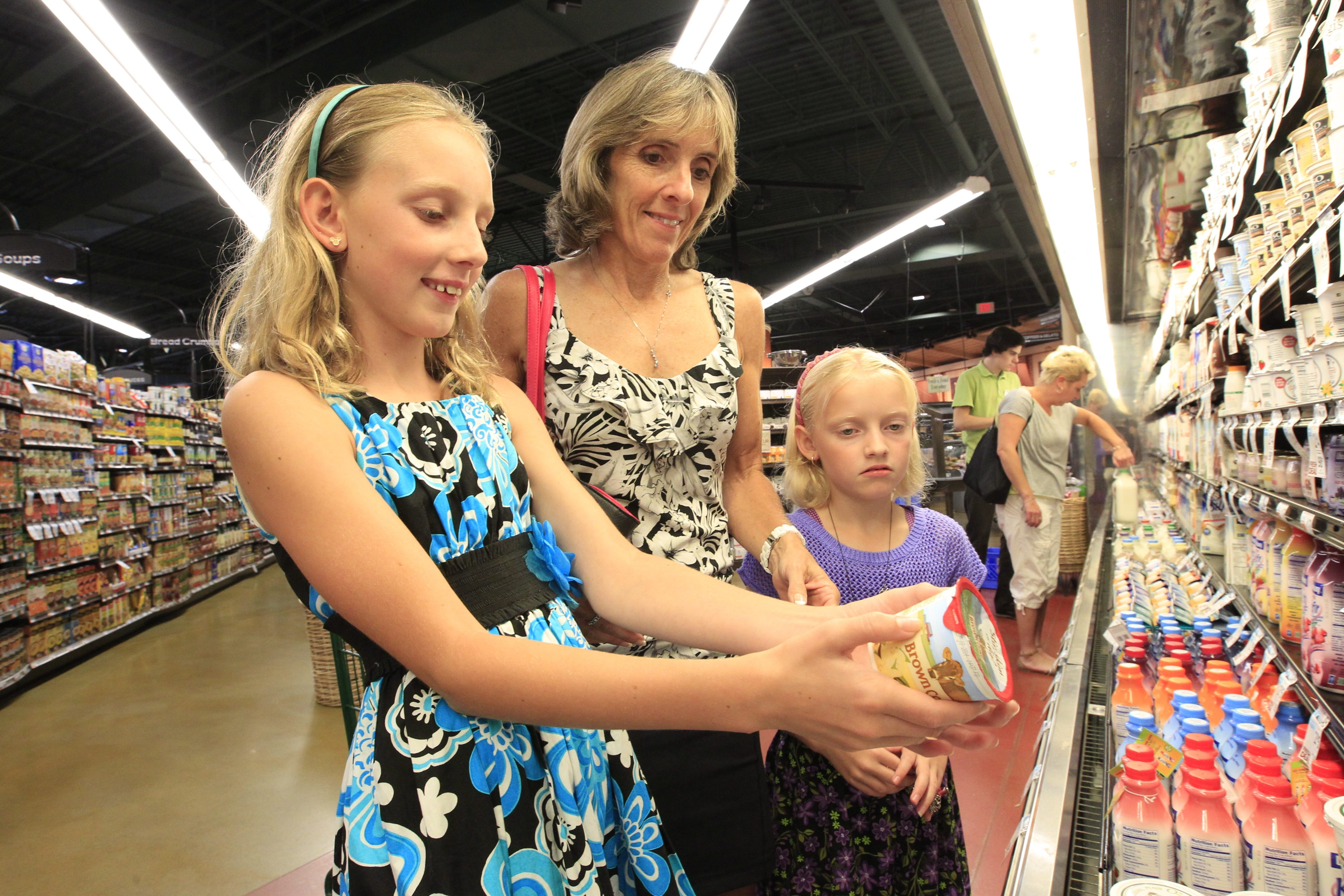 Carol DeNysschen, a registered dietitian, shops with her children Ashley, 10, and Jenna 8, for healthy back-to-school snacks at Orchard Fresh in Orchard Park on Aug. 26.