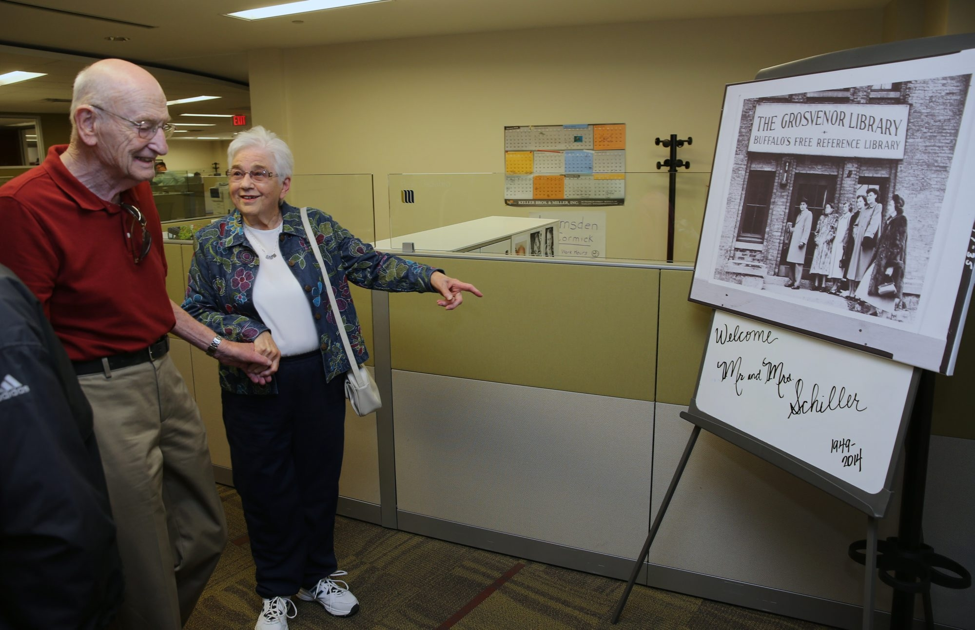 Harvey and Nancy Schiller look at an old photo from when the Cyclorama building was a library, as they celebrate their 65th anniversary Thursday at the spot where they first became engaged.