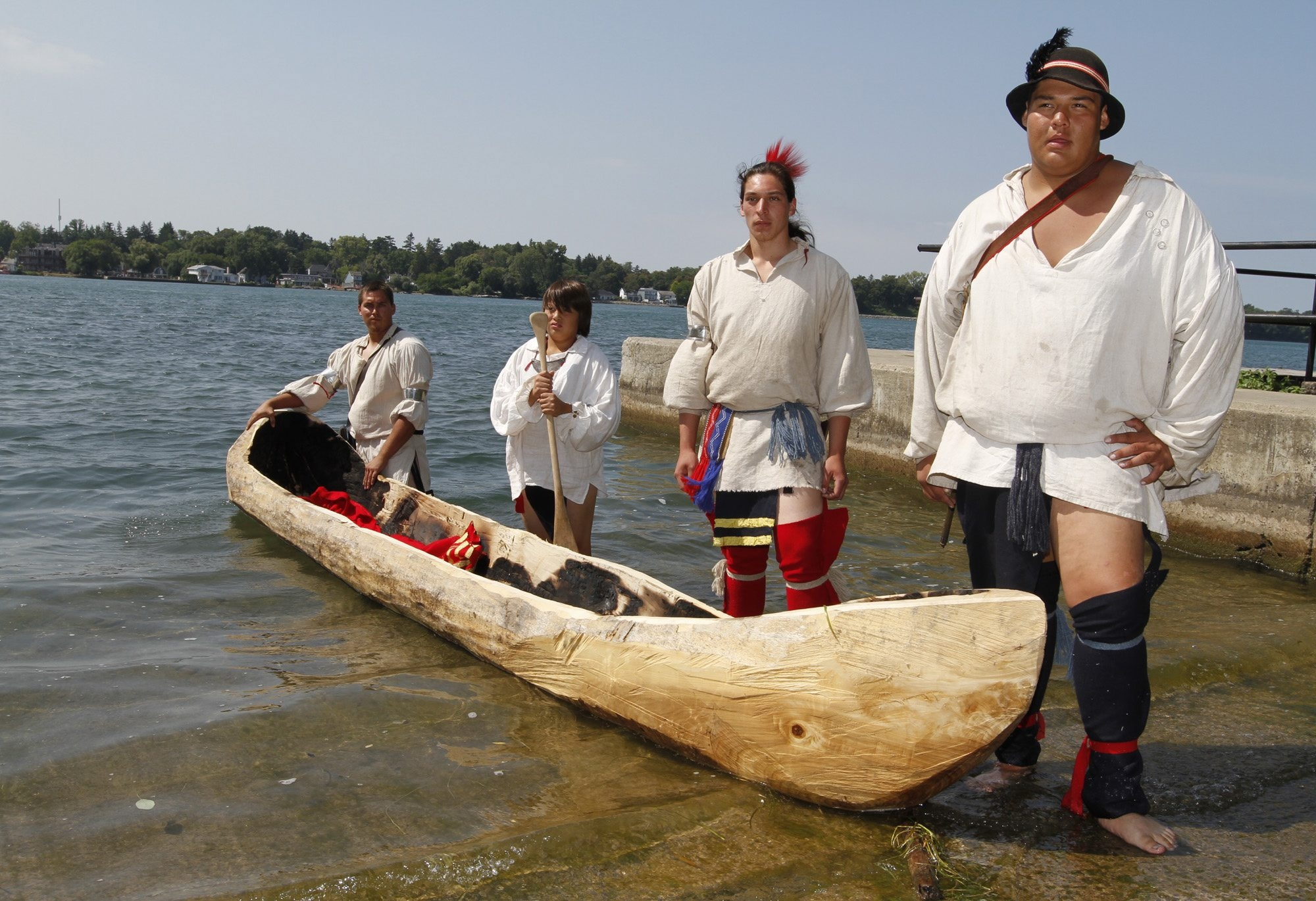 Native Americans Jacob Henry and Aidan Patterson, 11, left, paddled a dugout canoe on Tuesday. It was built by historical interpreters Marlin Wilson (Tuscarora) and Hawk Robinson (Seneca) built from scratch. See a photo gallery at BuffaloNews.com.