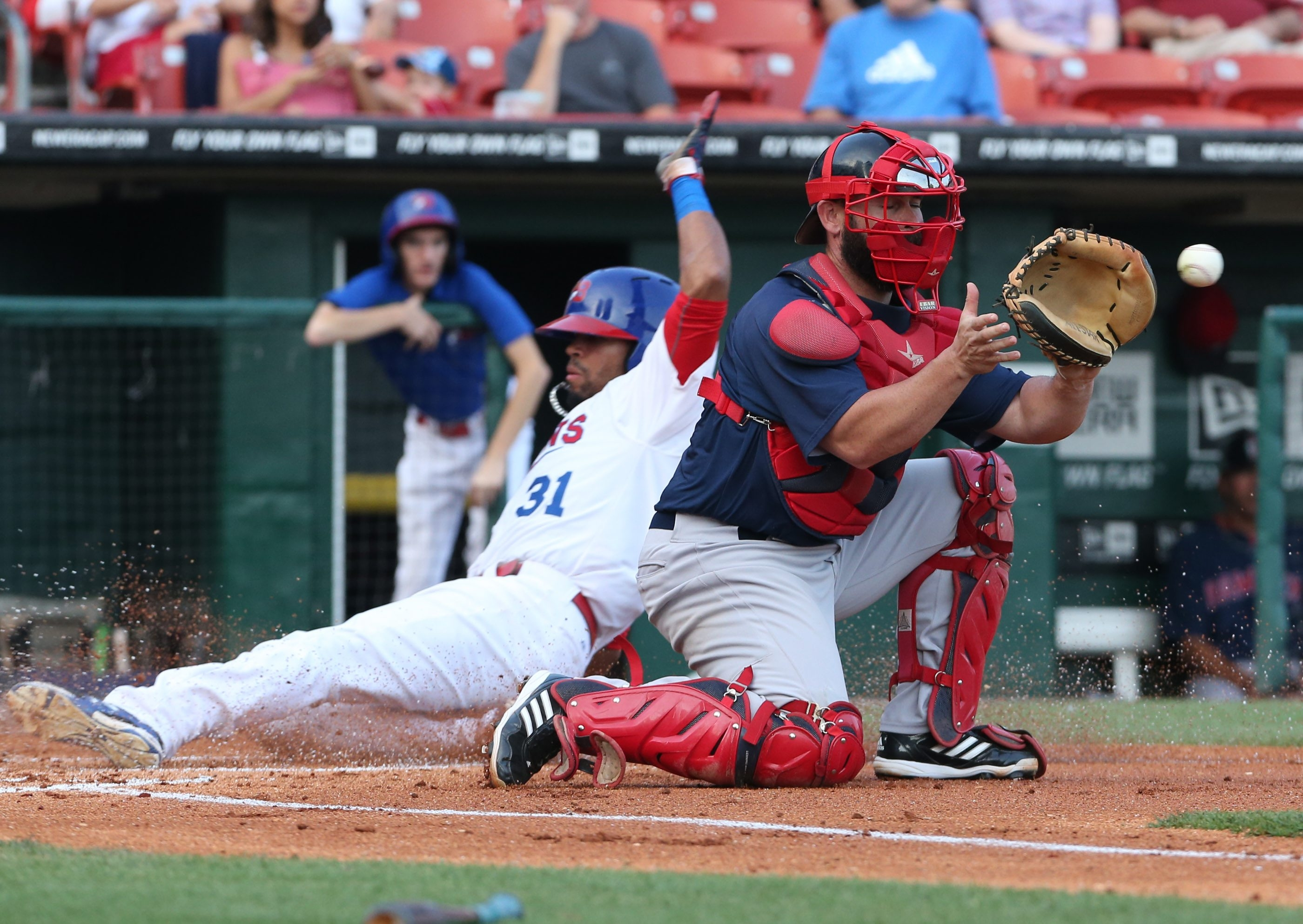 Bisons' Dalton Pompey slides across home plate for a run in front of PawSox catcher Dan Butler in the first inning.