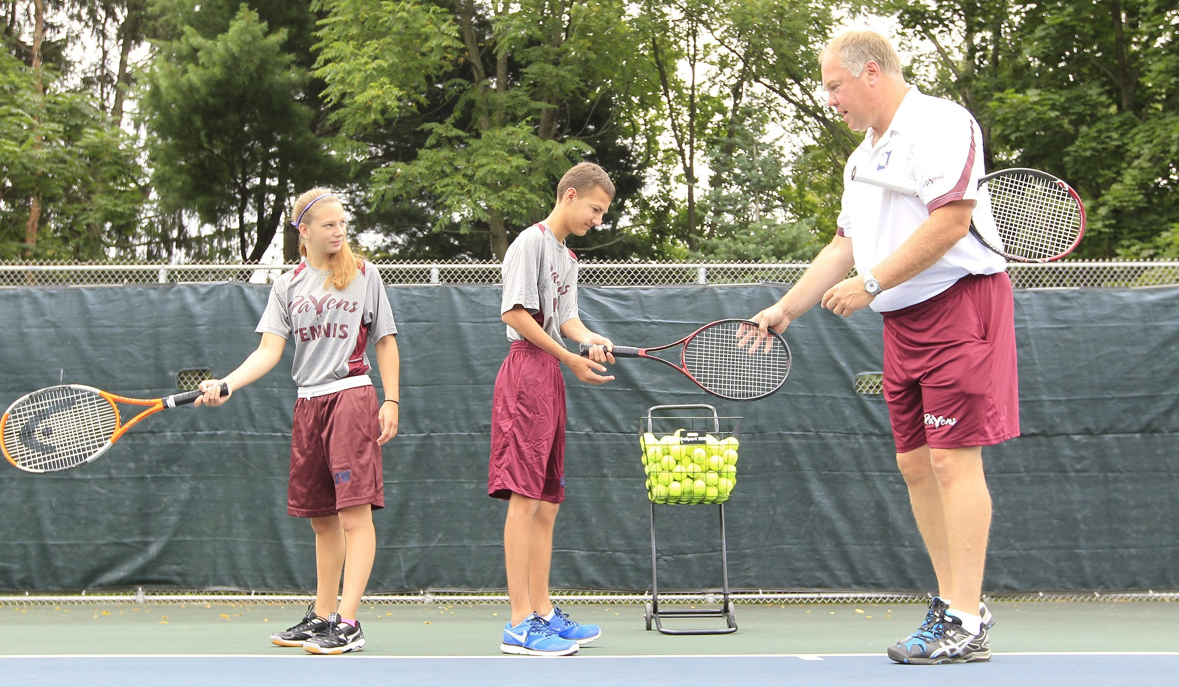 Gow school athletics director and tennis coach Mark Szafnicki instructs  Emily Todoro, 17, and Cole Wahler, 16.