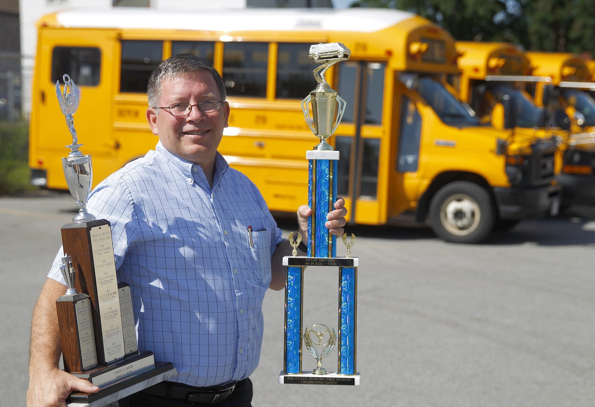 Depew Union Free School District bus driver Doug Sexton holds the first-place trophies he won for safe driving in the 2014 School Bus Safety Road-eo in Albany. Sexton, 52, of the Village of Lancaster, is also pastor of Hedstrom Memorial Baptist Church in Cheektowaga.