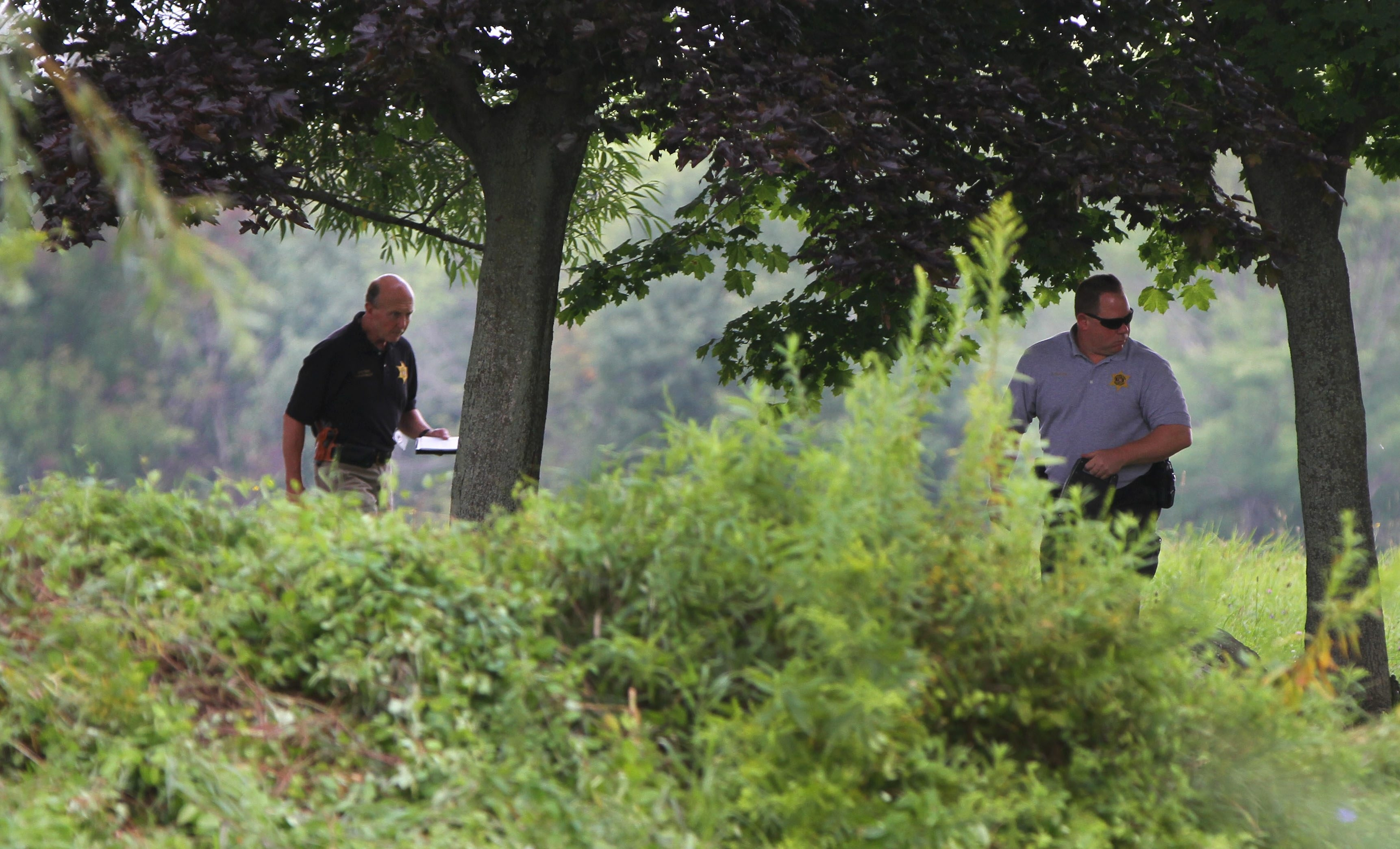 Chautauqua County Sheriff Deputies search a pond in the back of the home of Mary Whitaker on Titus Rd. in the Town of Westfield Friday, August 22, 2014.   (Mark Mulville/Buffalo News)