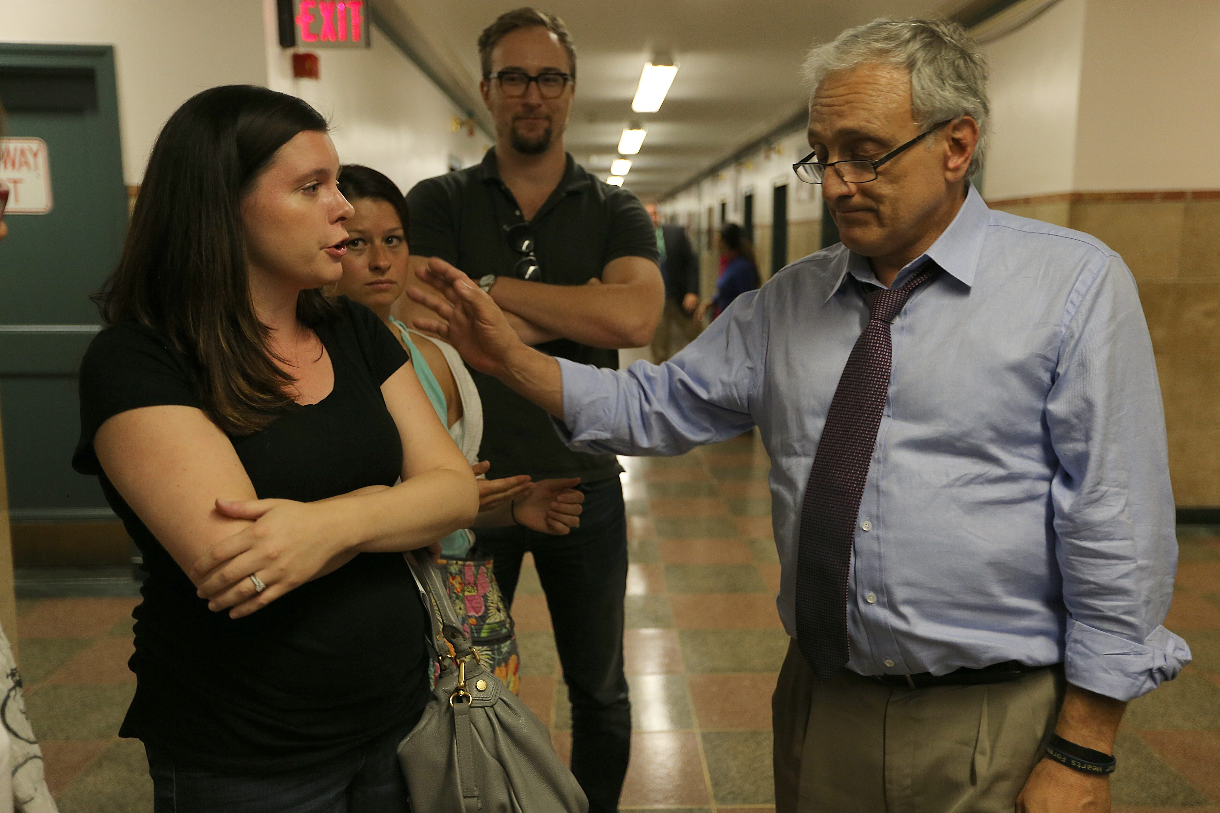 Buffalo School Board member Carl Paladino talks with Kelly Bohlen,  left, and several other teachers from Star Academy that were given layoff notices, outside the Board offices in Buffalo's City Hal on Wednesday.