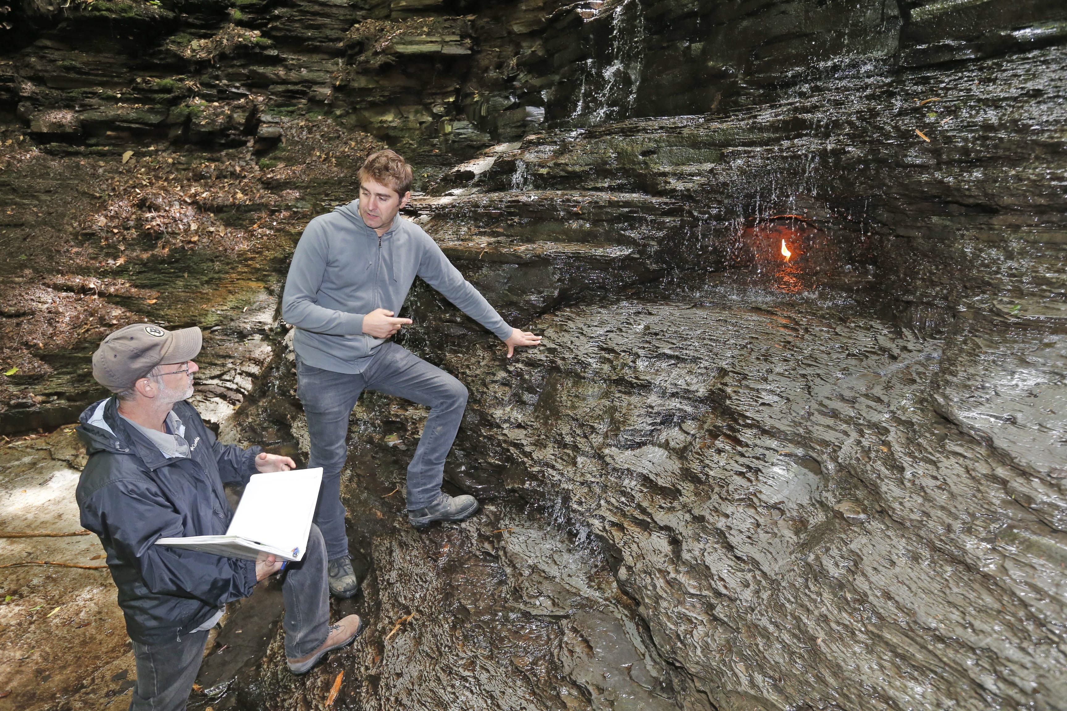 """Director Glenn Kirschbaum, left, and host Tory Belleci of """"MythBusters,"""" discuss filming near the Eternal Flame at Chestnut Ridge on Friday. A crew was in town to produce a show for Travel Channel that should air in the first quarter of 2015."""