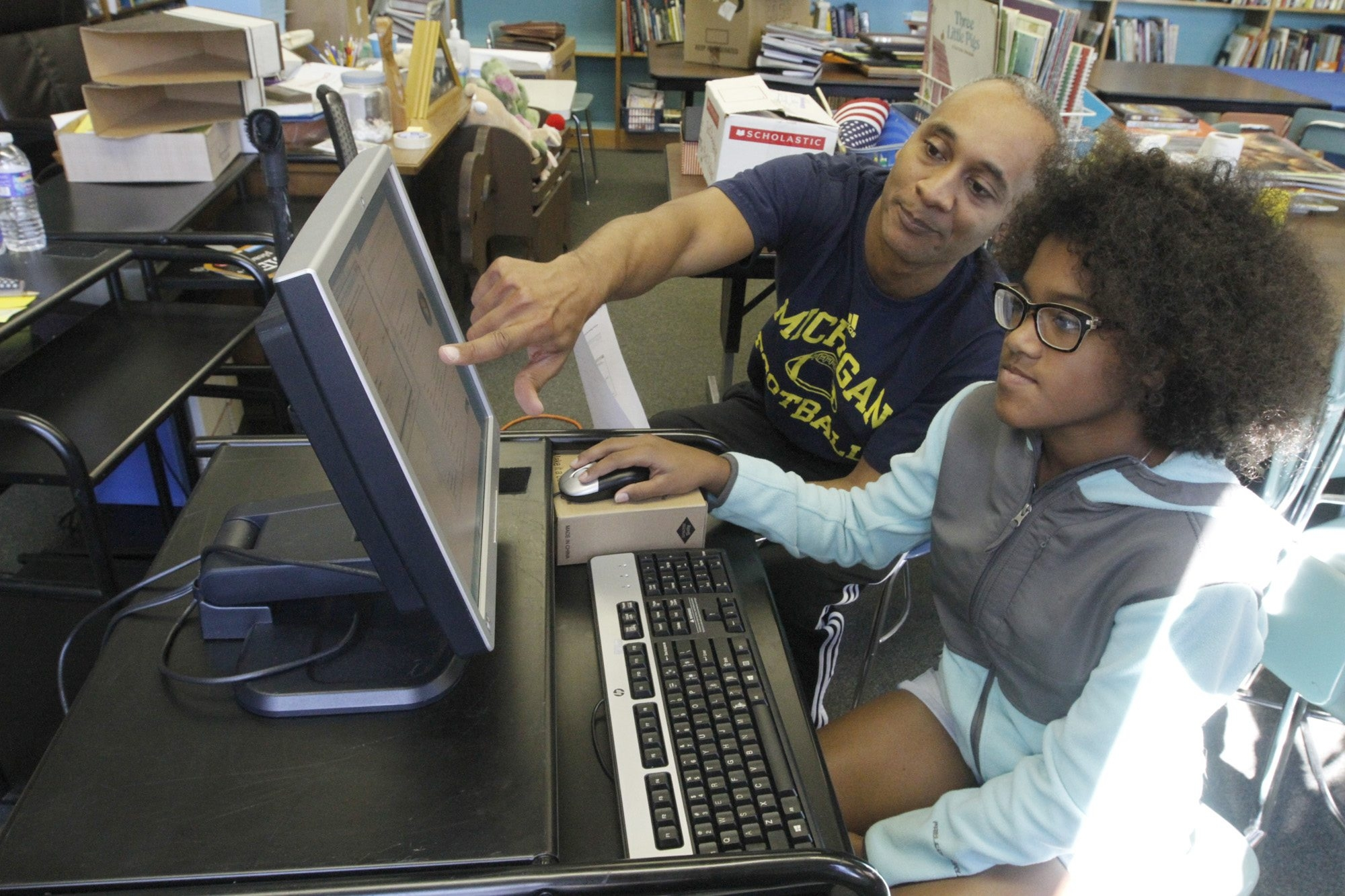 Darand Land, left, of Symantic, and his daughter Alicia configure a computer as they work with the Educational Technology Foundation of Western New York at Our Lady of Black Rock School.