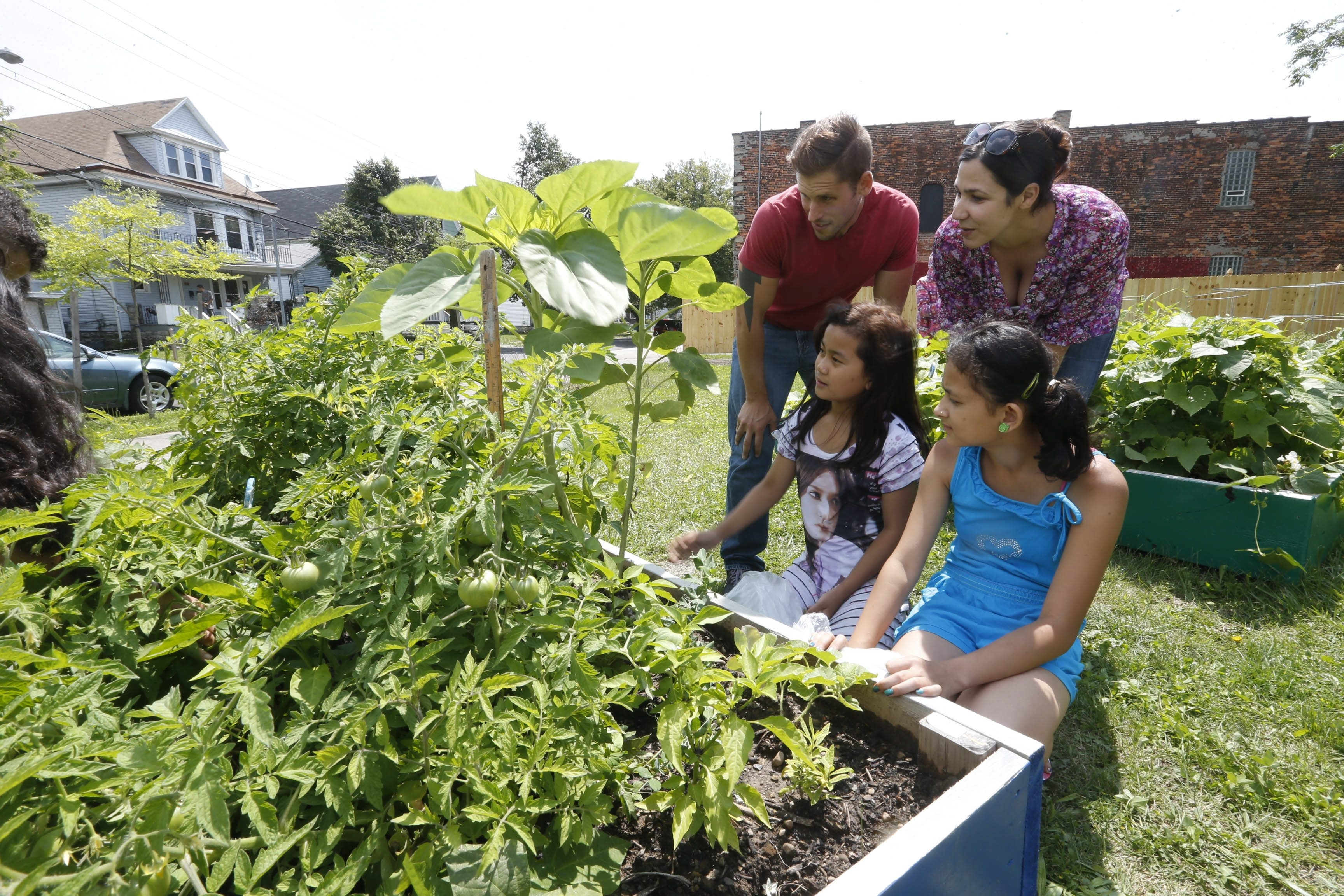 Derek Nichols and Melissa Fratello, both with Grassroots Gardens, check the progress of the School 18 garden with Hser Wah, 11, front left, and Reya Chhetri, 11.