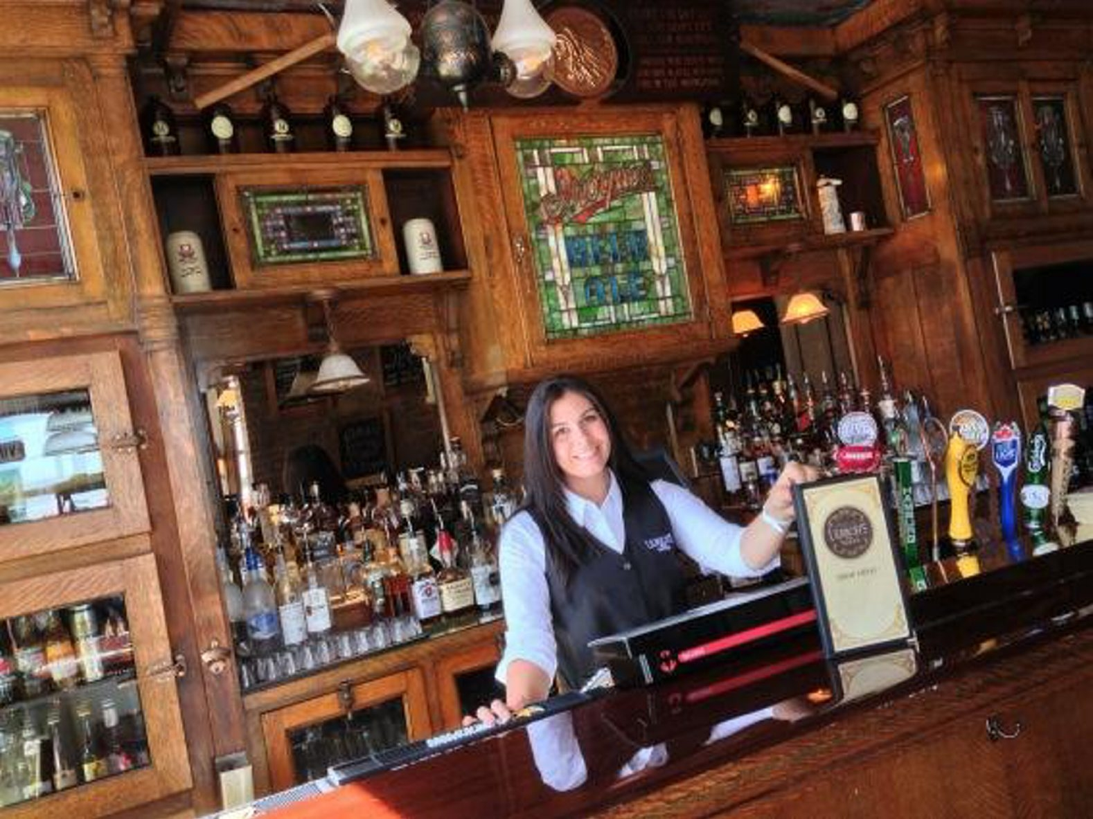 Bartender Molly DiBlasi puts out the new drink menu at Ulrich's  1868 Tavern in preparation for today's grand opening. (John Hickey/Buffalo News)