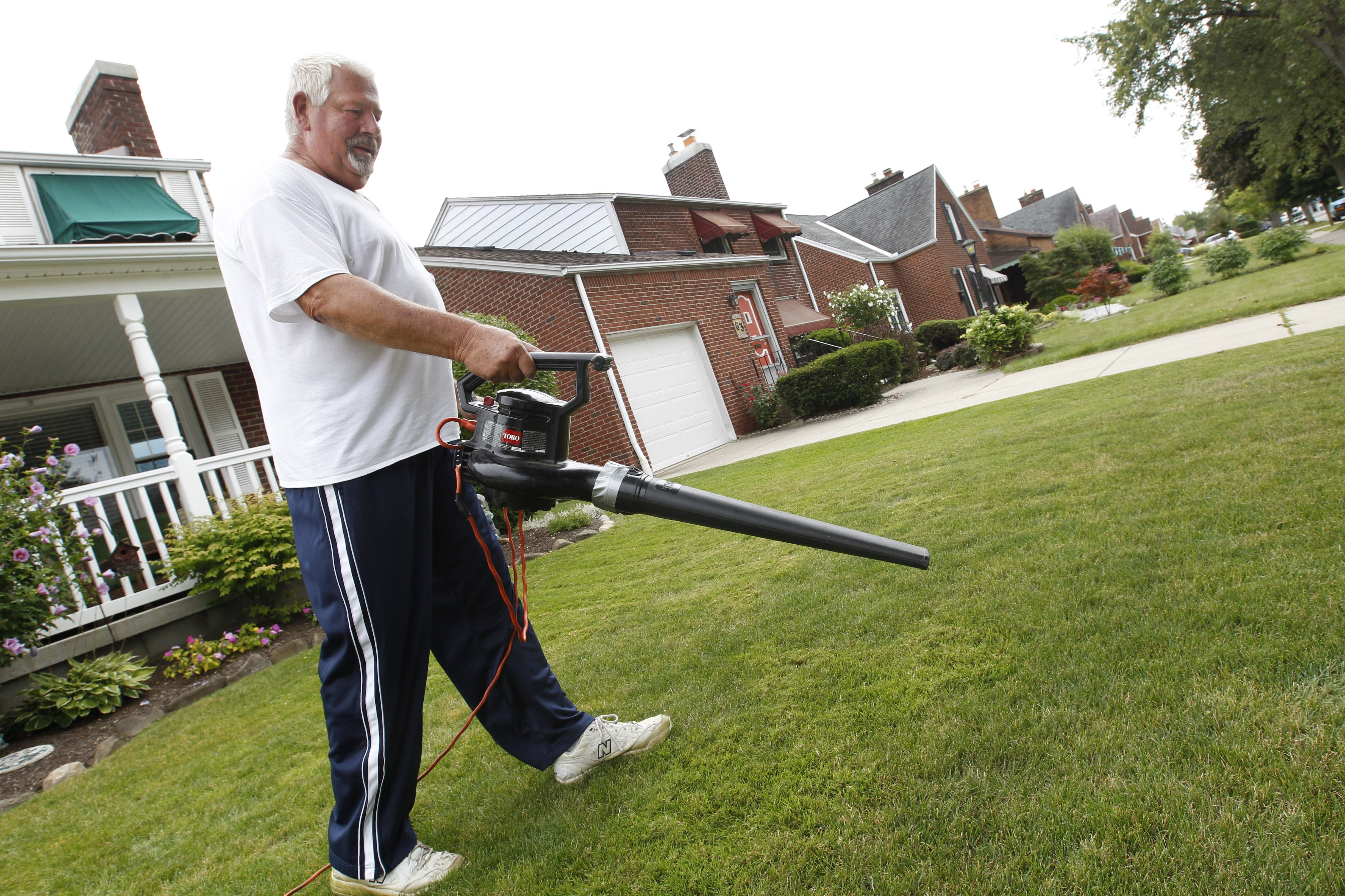 Clark Miller, of Kenmore, uses a leaf blower after cutting his grass. Miller prefers the noisy blower because it's easier than raking.