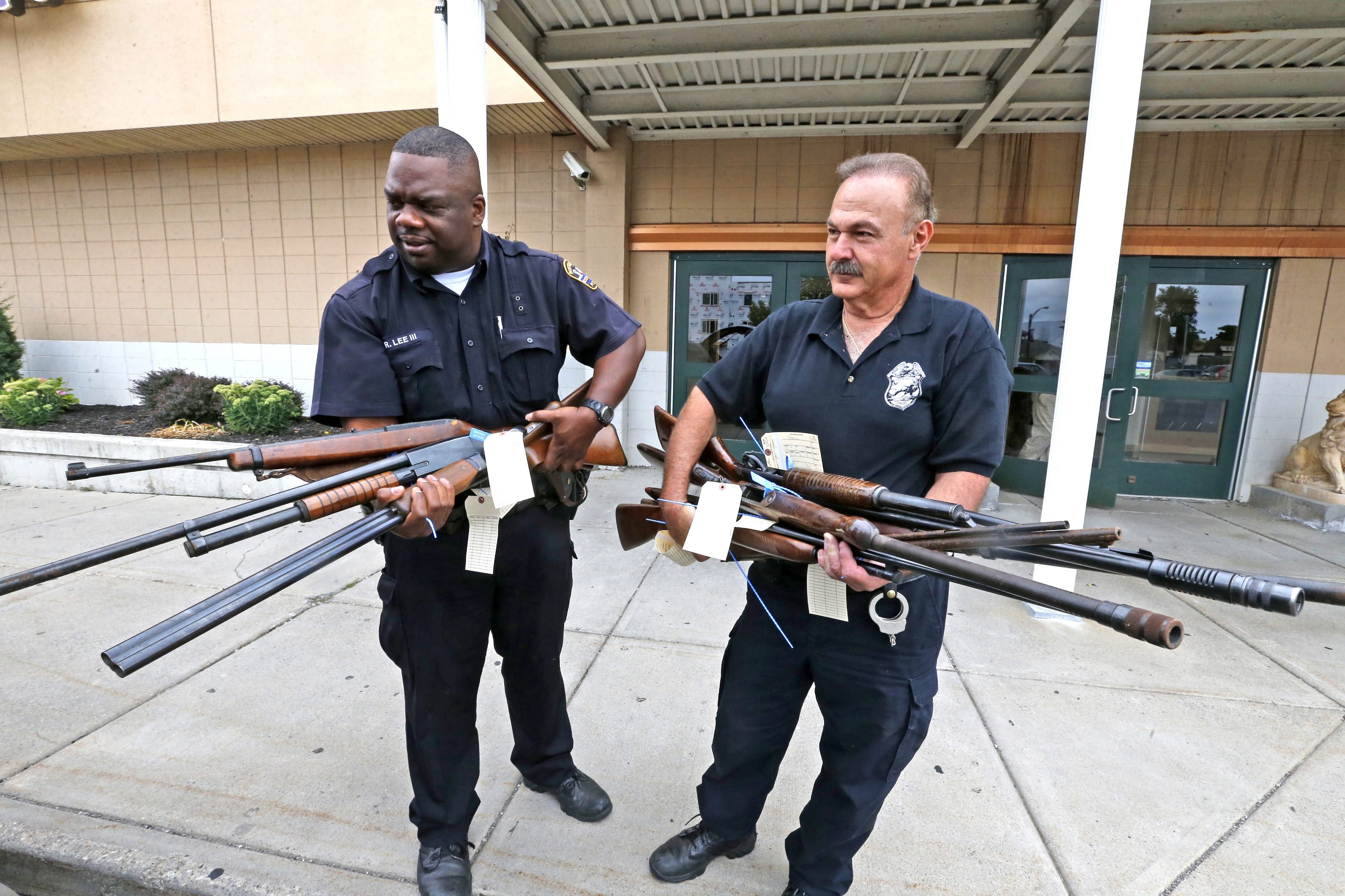 Buffalo Police Officer Robert Lee III , left, and Lt. Steve Nichols, carry rifles and shotguns that were turned in during Buffalo's gun buyback program at True Bethel Baptist Church on East Ferry Street on Aug. 16. This location took in 100 guns by noon. (Robert Kirkham/Buffalo News)