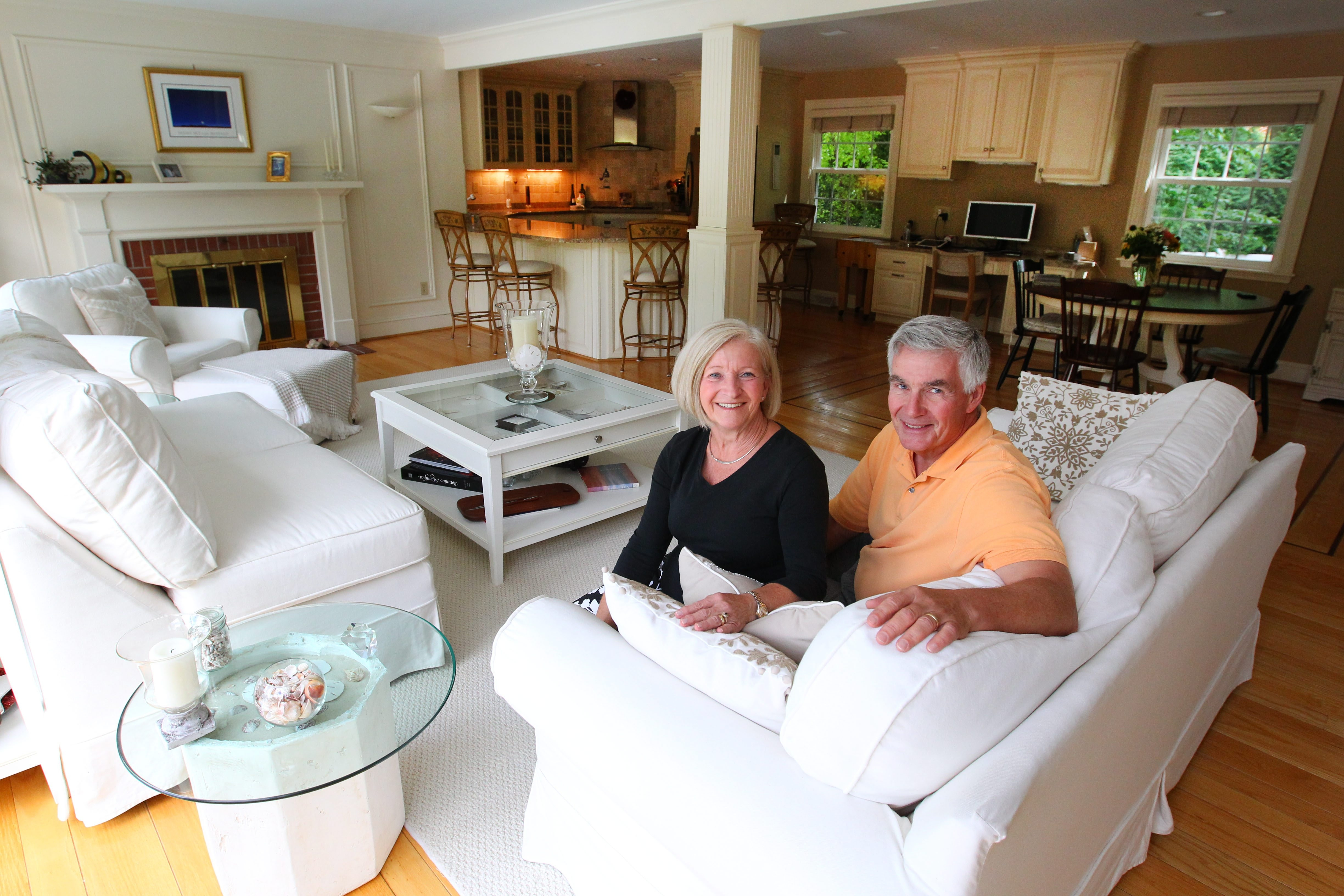 Open concept: Marcia and Nick Roth take a seat in the living room that leads to the kitchen they renovated about 10 years ago. Newer still is the half bath off the family room. A wine-themed mural in the kitchen, center, and a shadow box coffee table in the living room add personal touches.