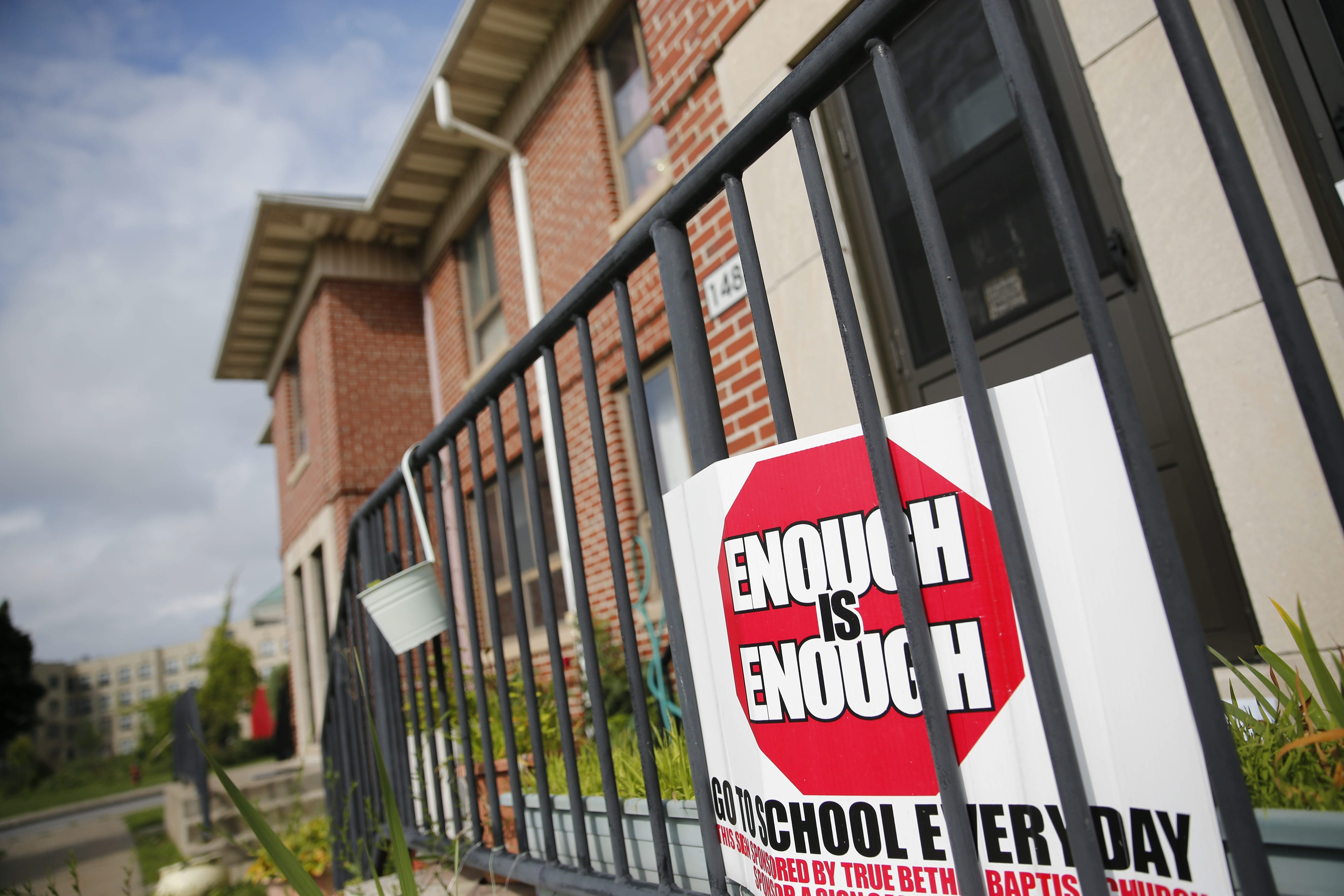 """A sign reads """"enough is enough"""" outside an apartment on Oakmont Avenue, nearby where a 14-year-old boy was killed and three other teens injured in a shooting Tuesday afternoon."""