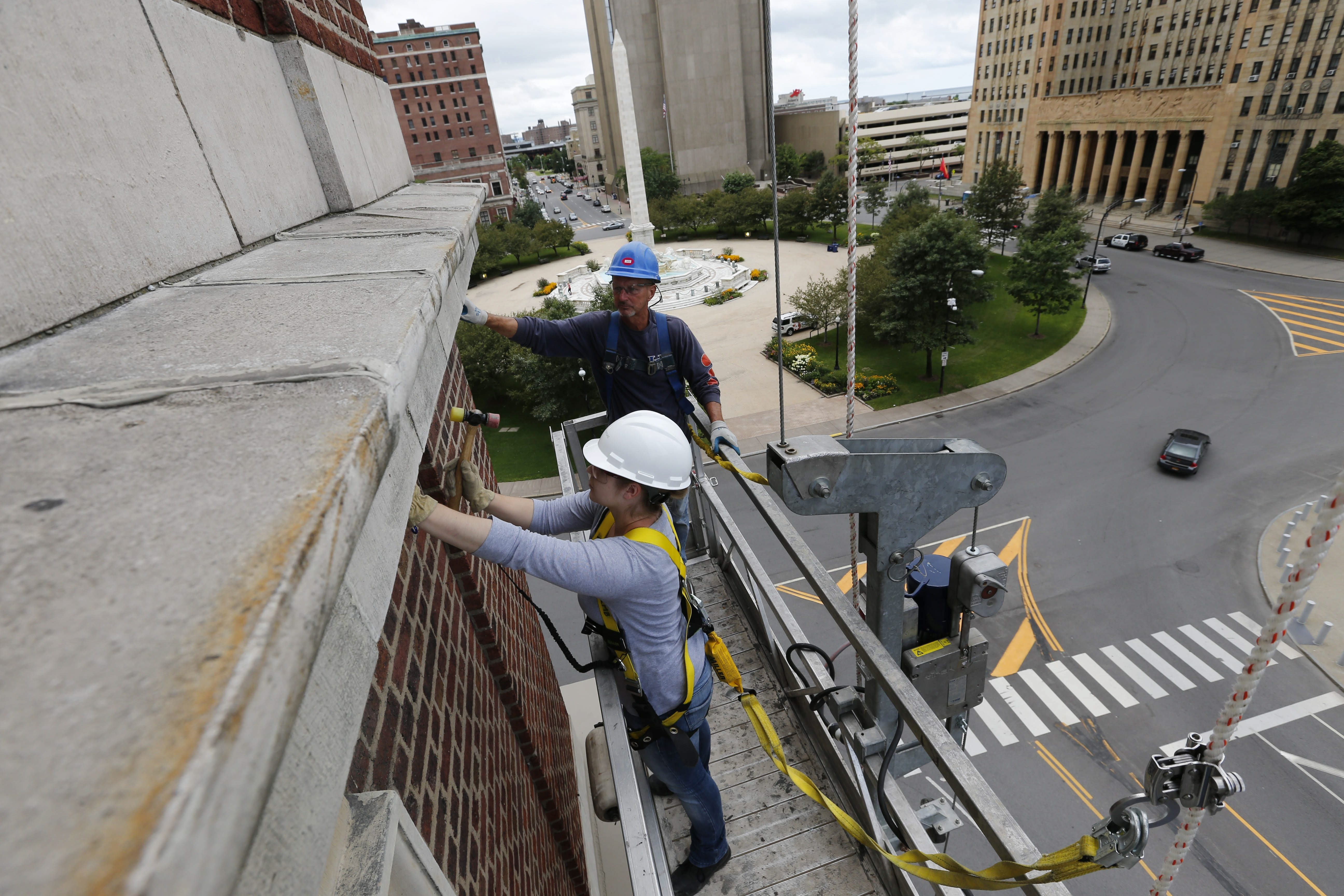 """Conservator Lurita Blank of WBM Engineering uses a process called """"sounding"""" to inspect the condition of the terra-cotta elements on the facade of Statler City on Tuesday while Gary Koz of Morris Masonry watches. The work is part of a $5.3 million exterior renovation."""