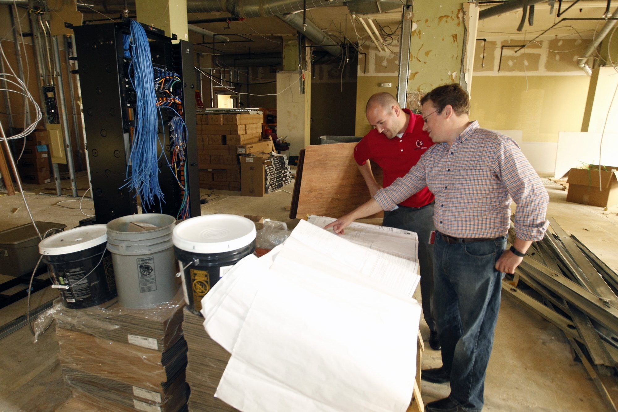 Steven M. Kiernan II, left, and Steven B. Raines, president and CEO, respectively, of Algonquin Studios, discuss plans in the company's space in the Brisbane Building. The 18,700-square-foot space is undergoing a $500,000 to $600,000 renovation.