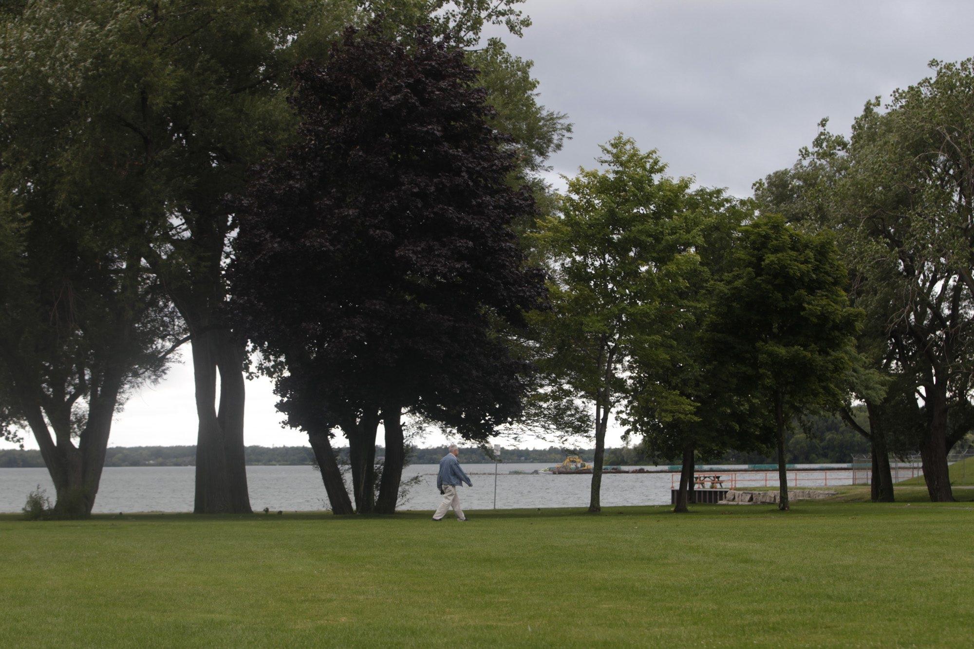 A pedestrian walks Tuesday on Aqua Lane in the Town of Tonawanda under overcast skies.