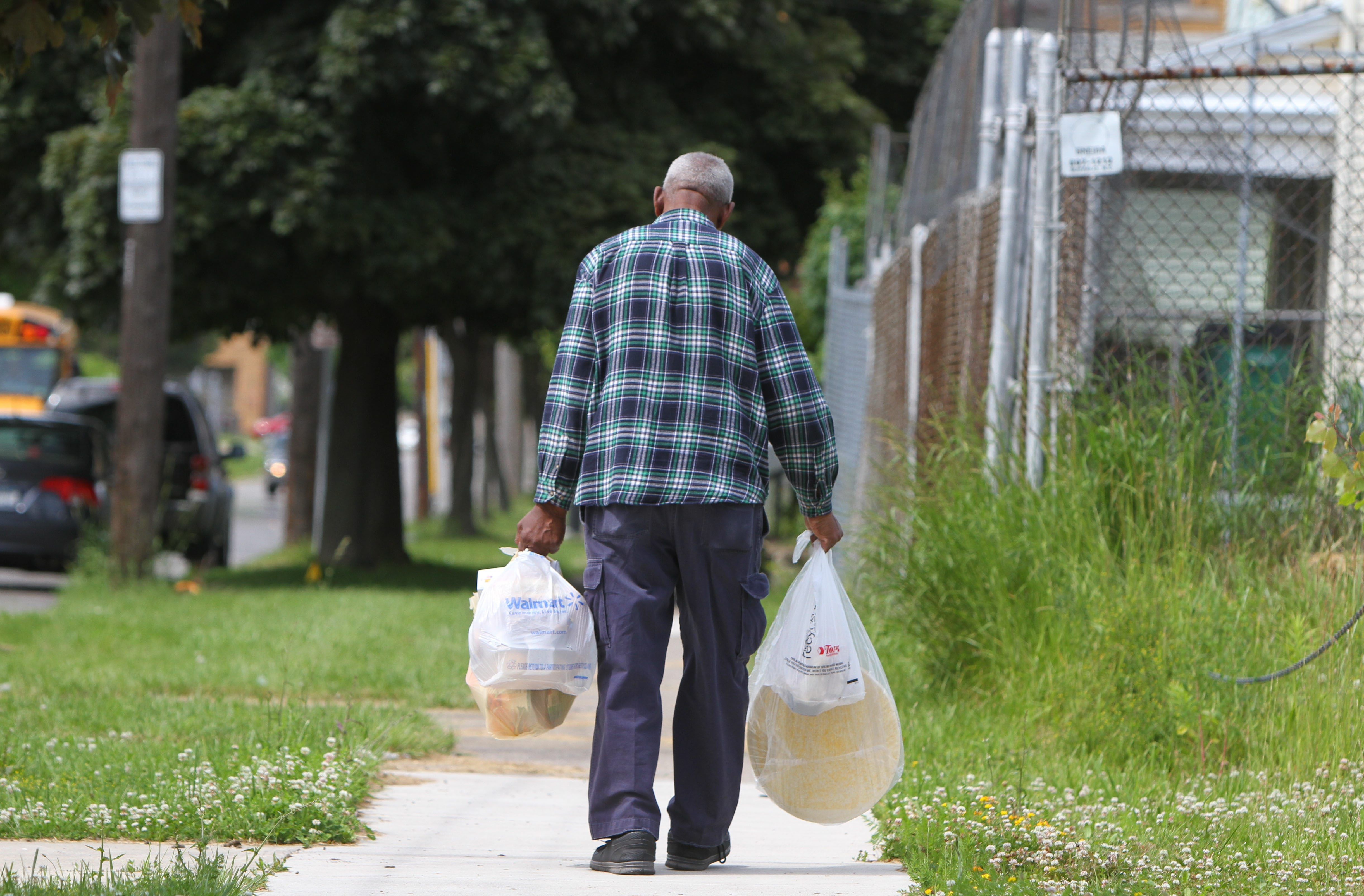 A man walks home with food from the Dream Center's food truck on Masten Avenue in Buffalo.