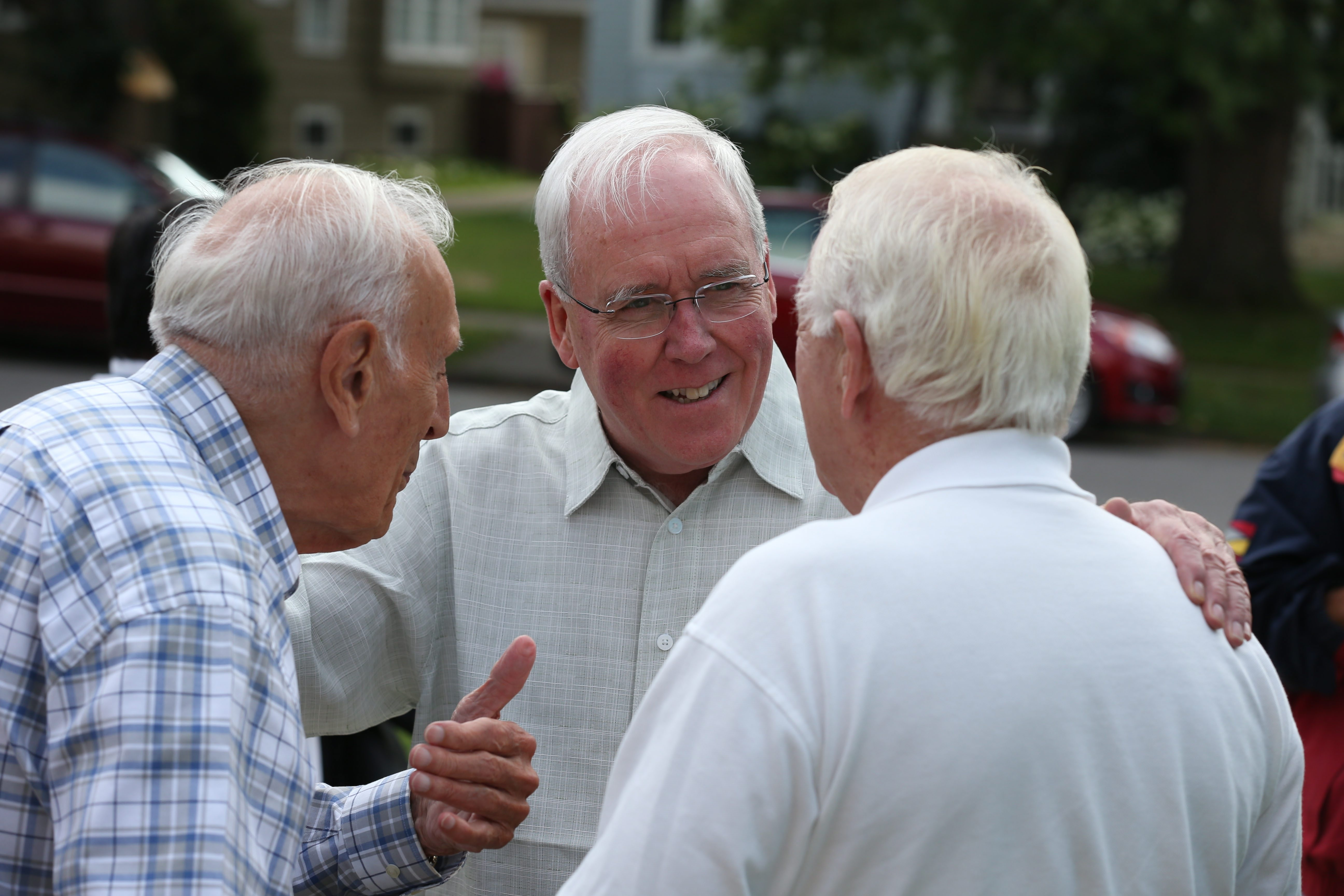 Bishop Richard J. Malone, center, talks with fellow priests outside St. Mark Church in Buffalo, during a casual barbecue for priests, Wednesday, July 31, 2014. {Photo by