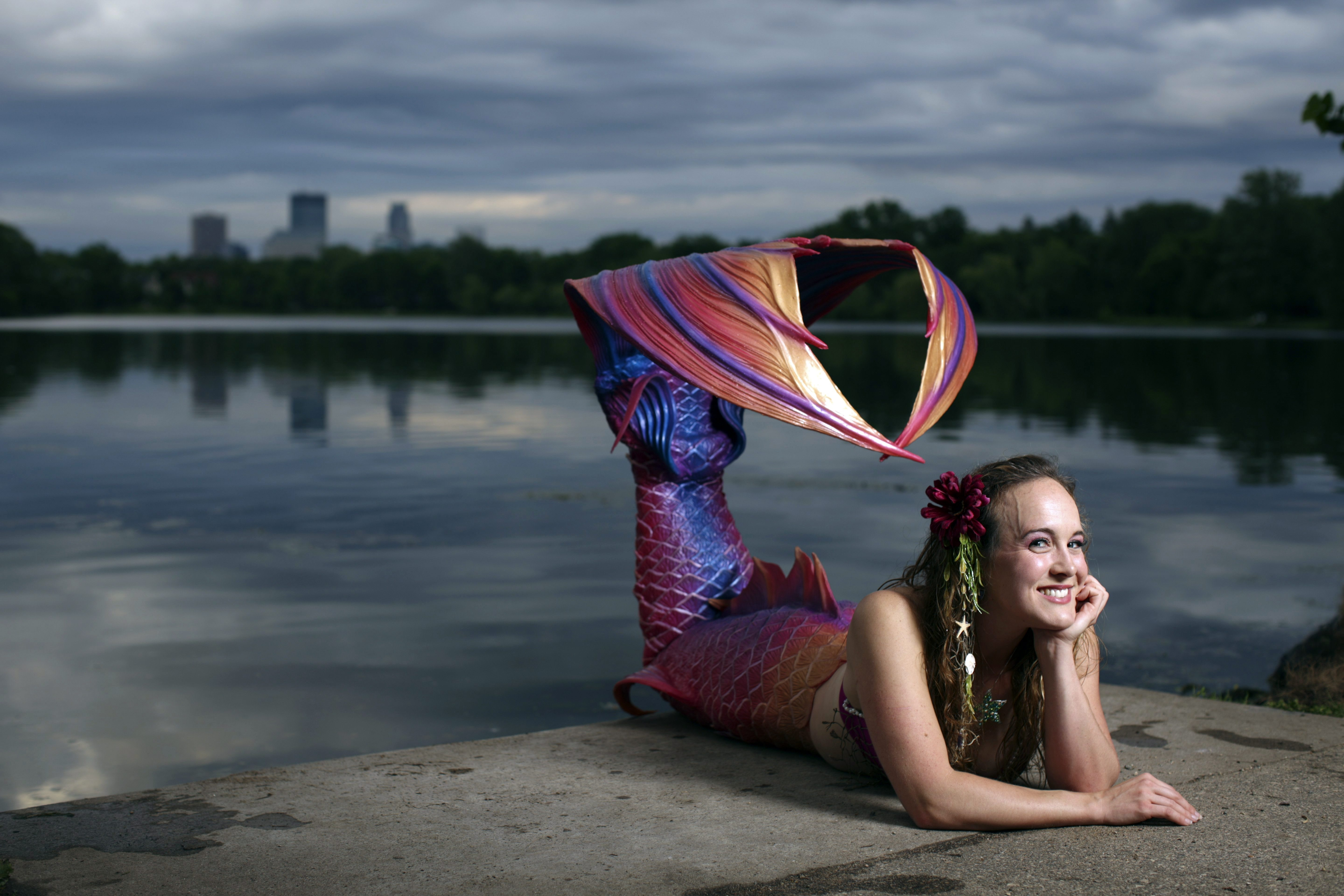 Allie Causin poses for a portrait on the shore of Lake of the Isles in Minneapolis in the mermaid tail she purchased from Bryn and Abby Roberts at Finfolk Productions.