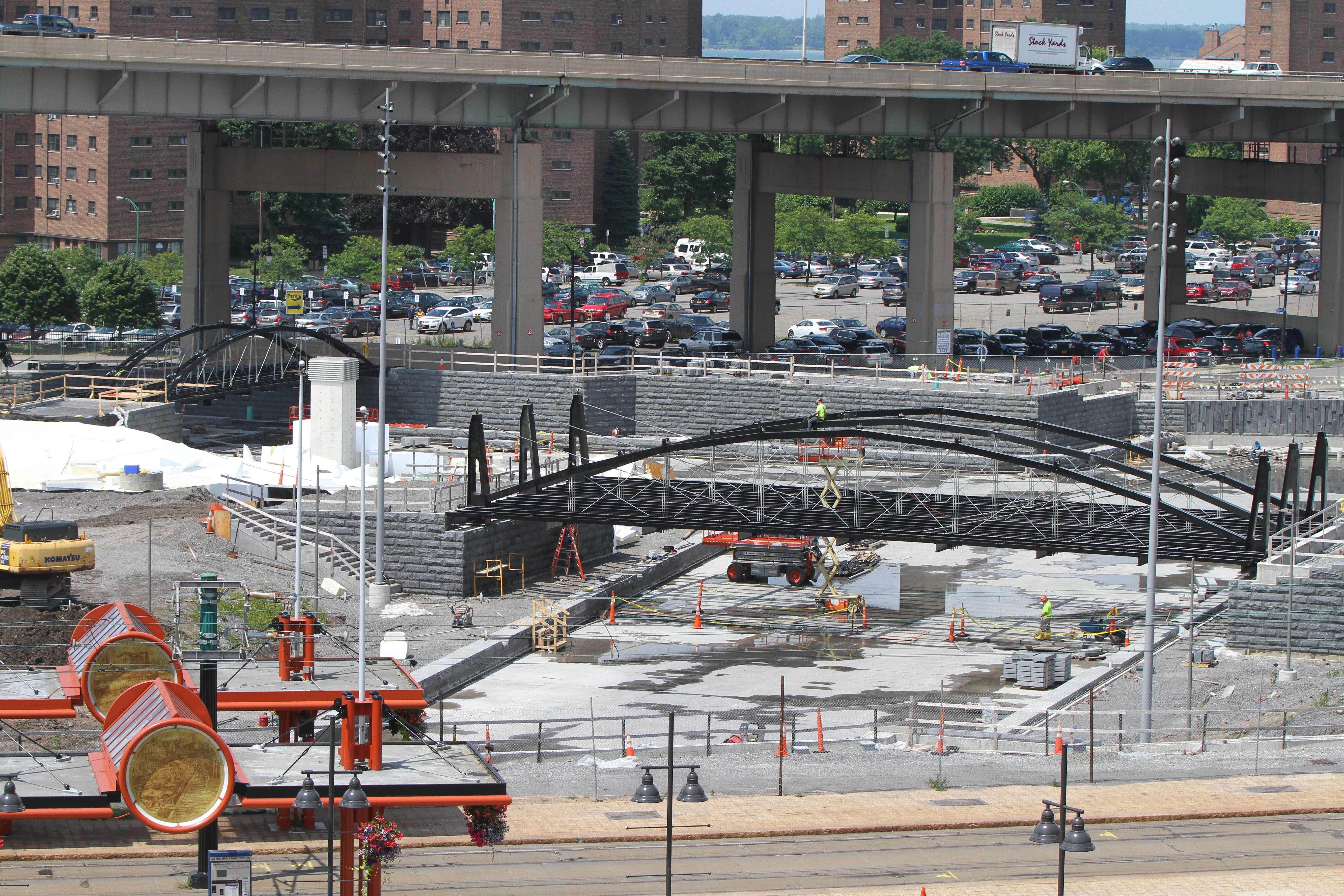 "Work continues on the bridges at Canalside in Buffalo. Most site work will be completed in September, with grass and paths making the space look ""habitable."""