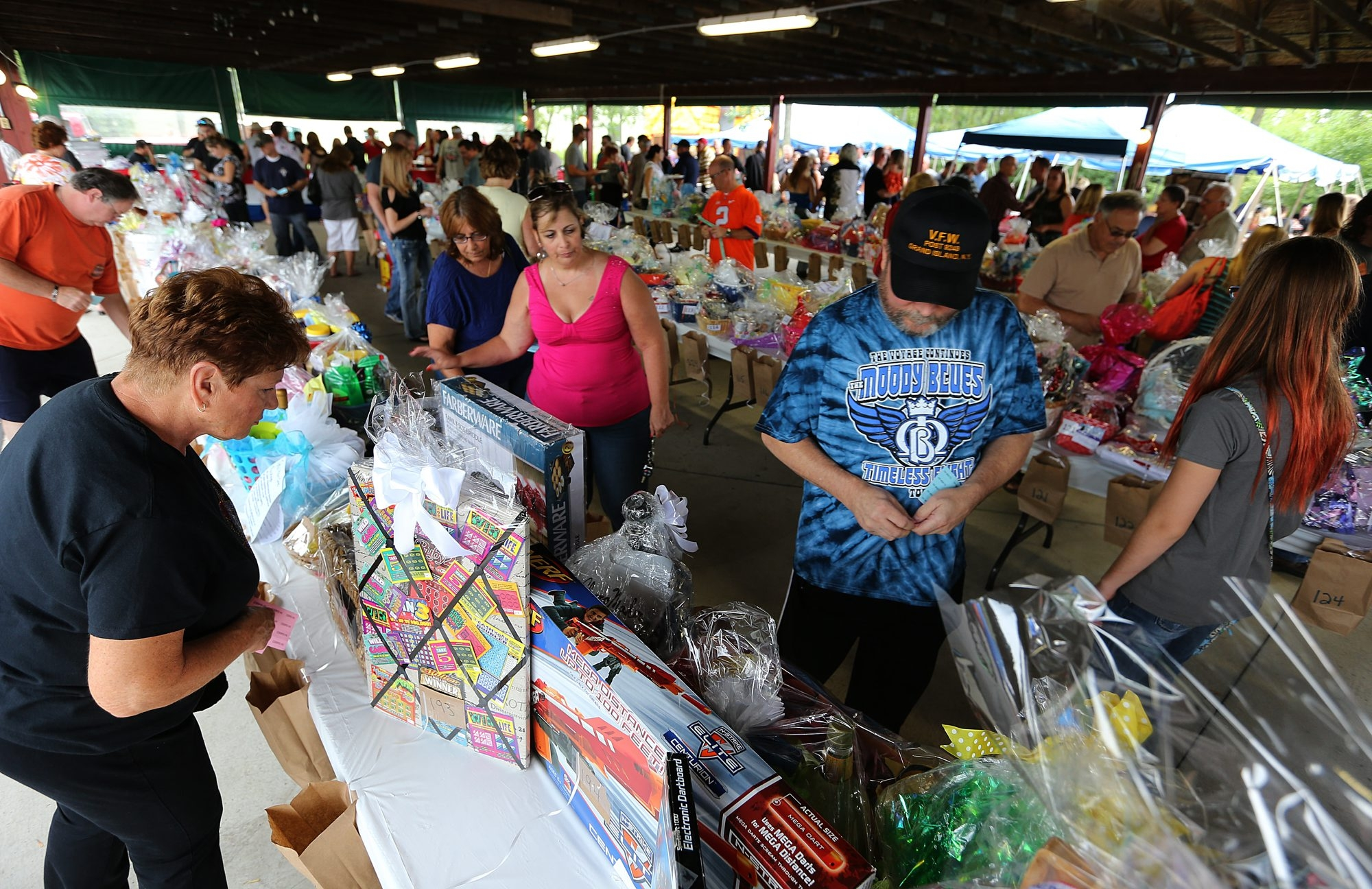 Attendees inspect baskets during a silent auction to benefit the family of William C. Sager Jr., who died at 28 on Thursday nearly three months after the assault incident at Molly's Pub. The event was held at Charles N. DeGlopper Memorial Post 9249, VFW, on Grand Island.