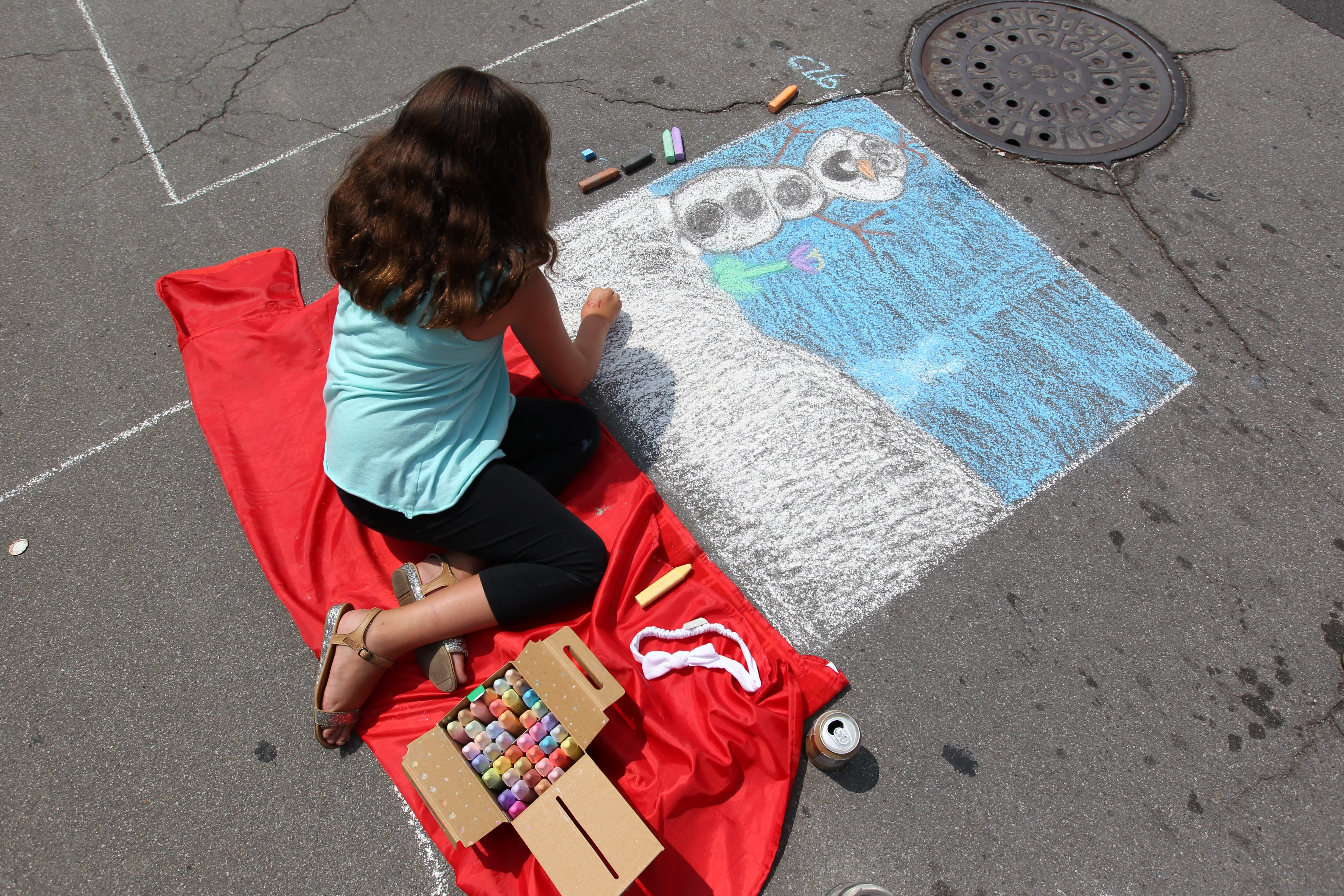 """Haley Roberts of Buffalo works on a drawing inspired by the movie """"Frozen"""" during the third annual Chalkfest Buffalo on Washington Street Saturday."""