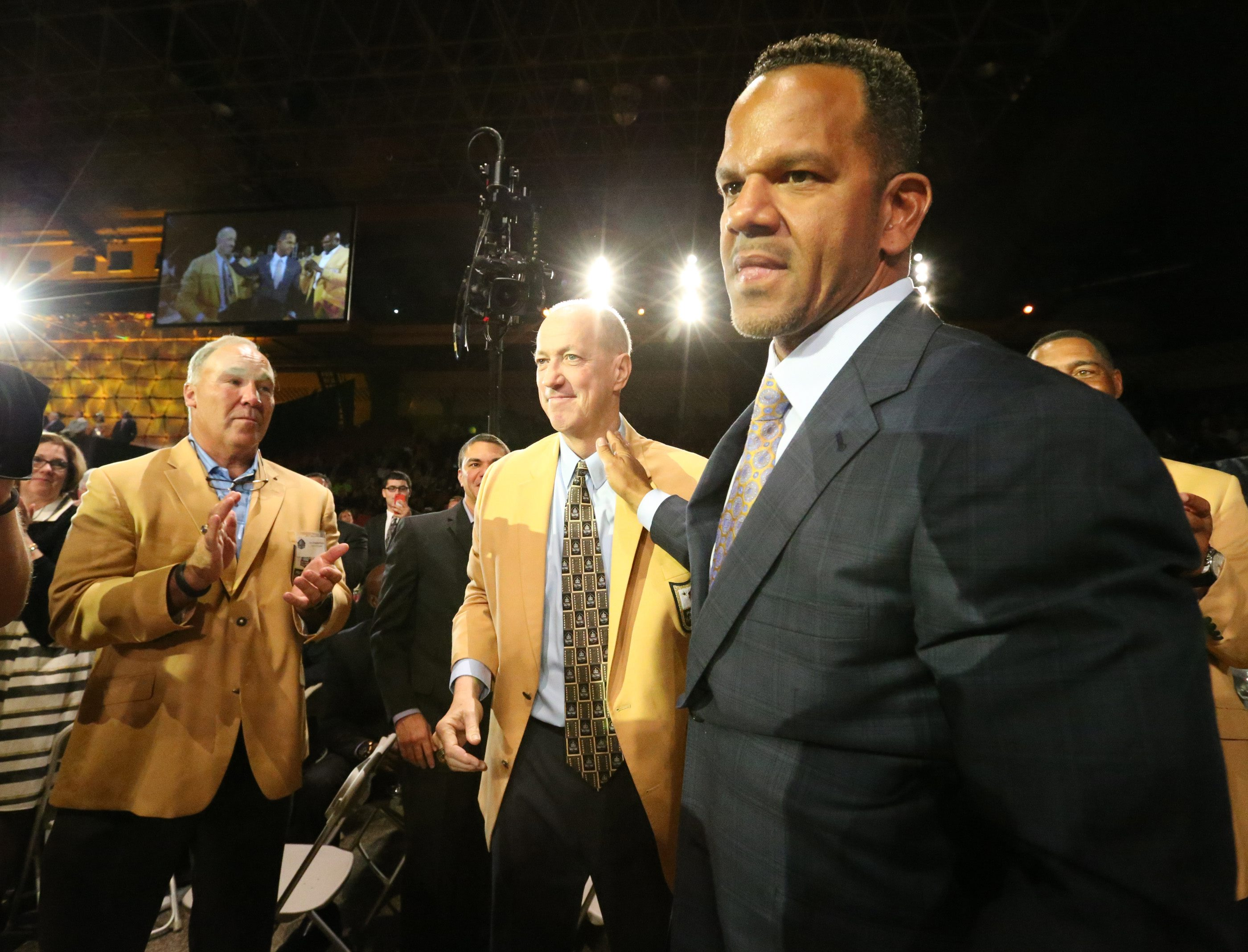 Buffalo Bills Hall of Famers Joe Delamielleure and Jim Kelly applaud as Andre Reed heads to the stage to receive his gold jacket.  (James P. McCoy/Buffalo News)