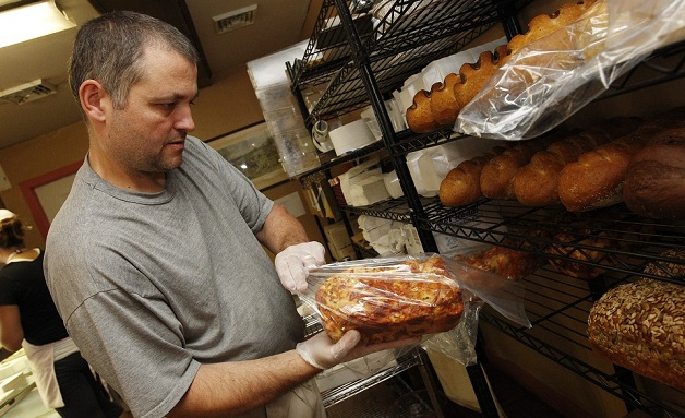 McDuffies Bakery owner Brian Thomas bags some of the fresh bread at the counter after it cools. (Sharon Cantillon / Buffalo News)